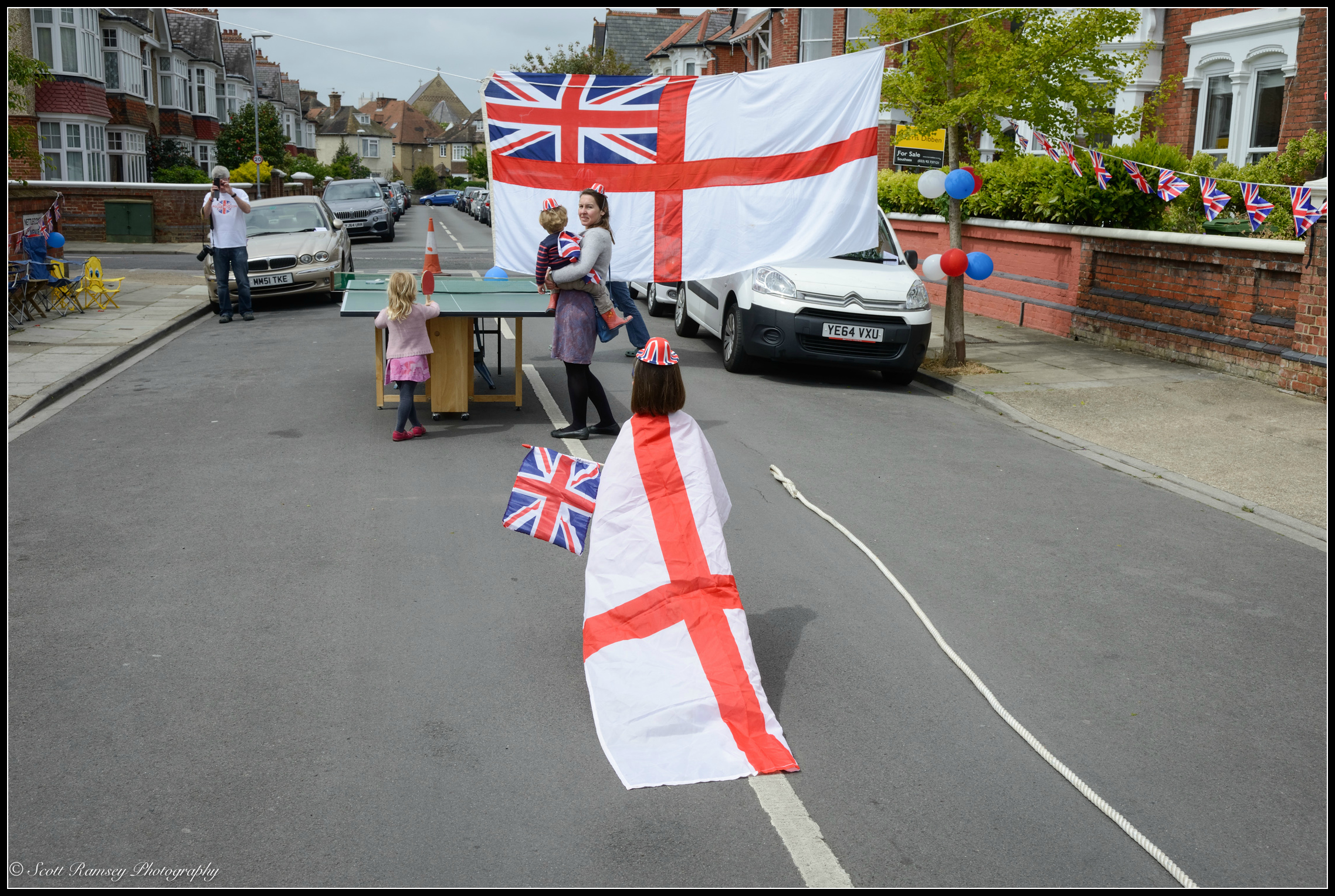 A girl wearing a Saint George's flag as a cloak and holding a union jack flag walks along  Nettlecombe Avenue in Southsea, Portsmouth during the VE Day70th   anniversarystreet party. © Scott Ramsey Photography.