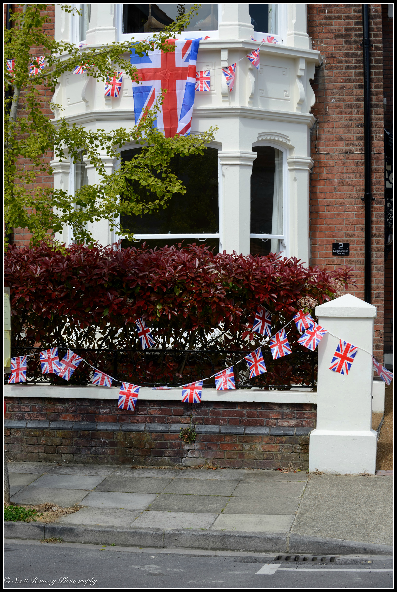 Flags and bunting hang outside a house in Southsea during a VE Day 70th Anniversary street party. © Scott Ramsey Photography.