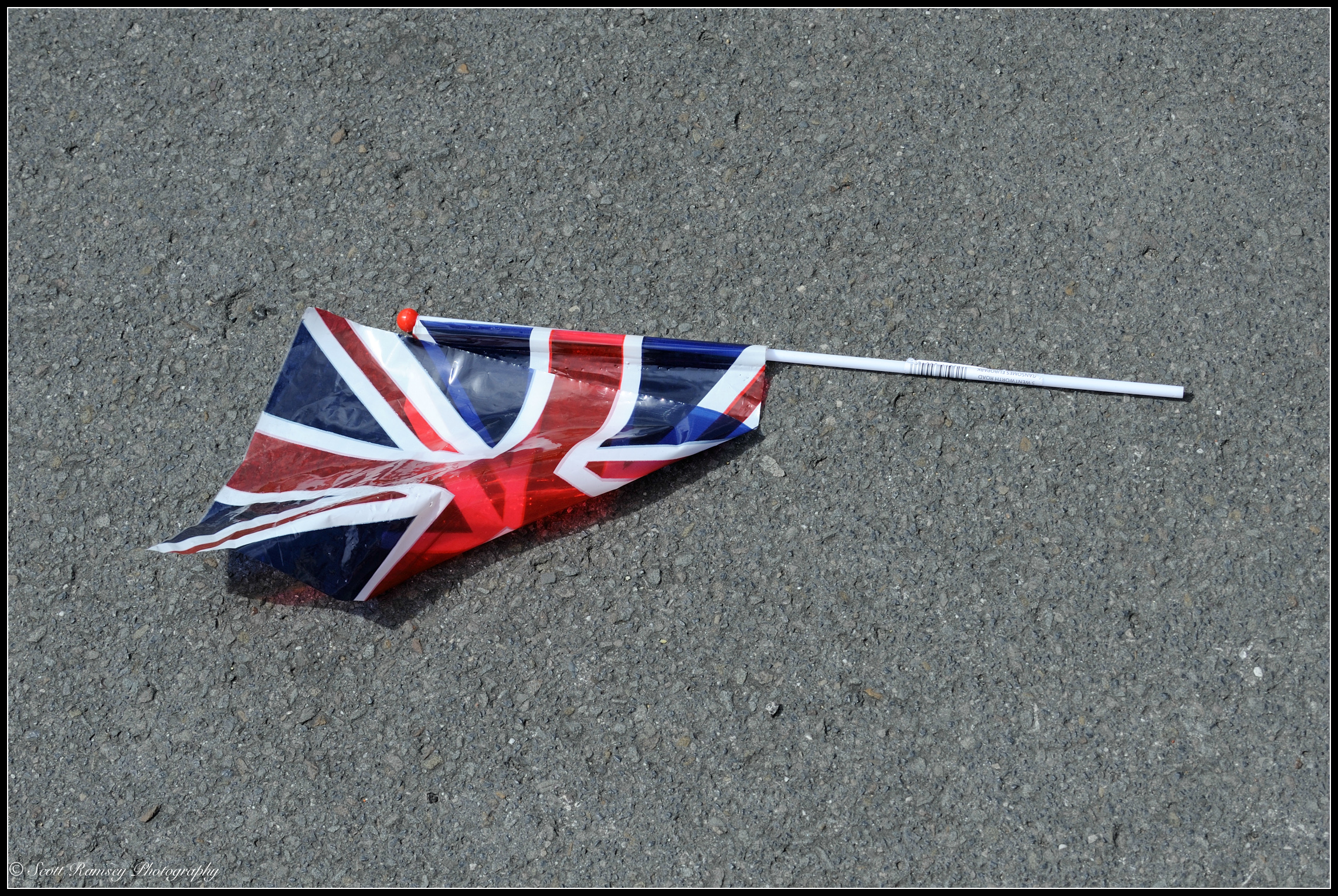 A union jack flag left on the road during a VE Day street party in Southsea, UK. © Scott Ramsey Photography.