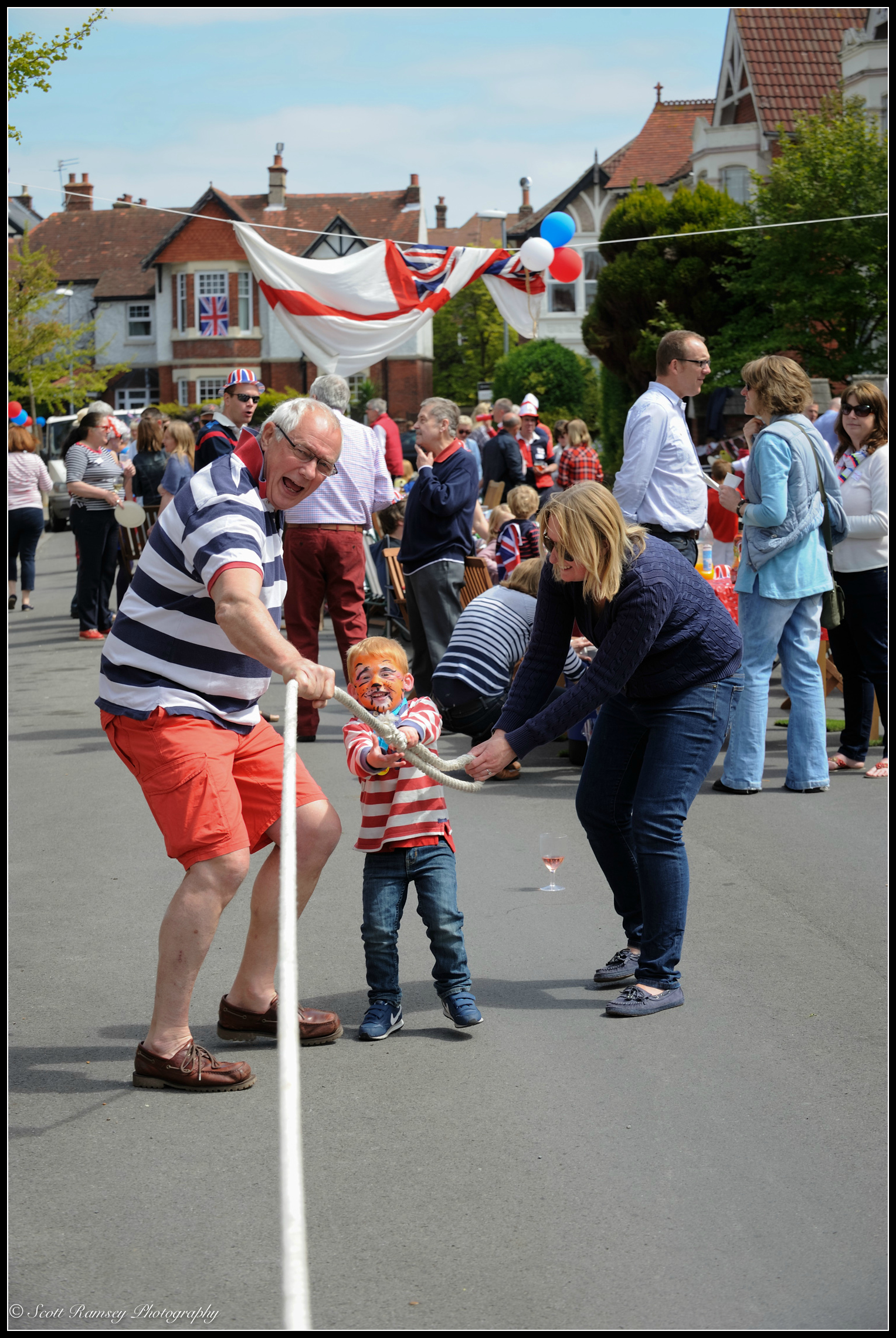 A man helps a young boy pull on a large rope during a tug of war match at the VE Day street party in Southsea, Portsmouth, UK. © Scott Ramsey Photography.