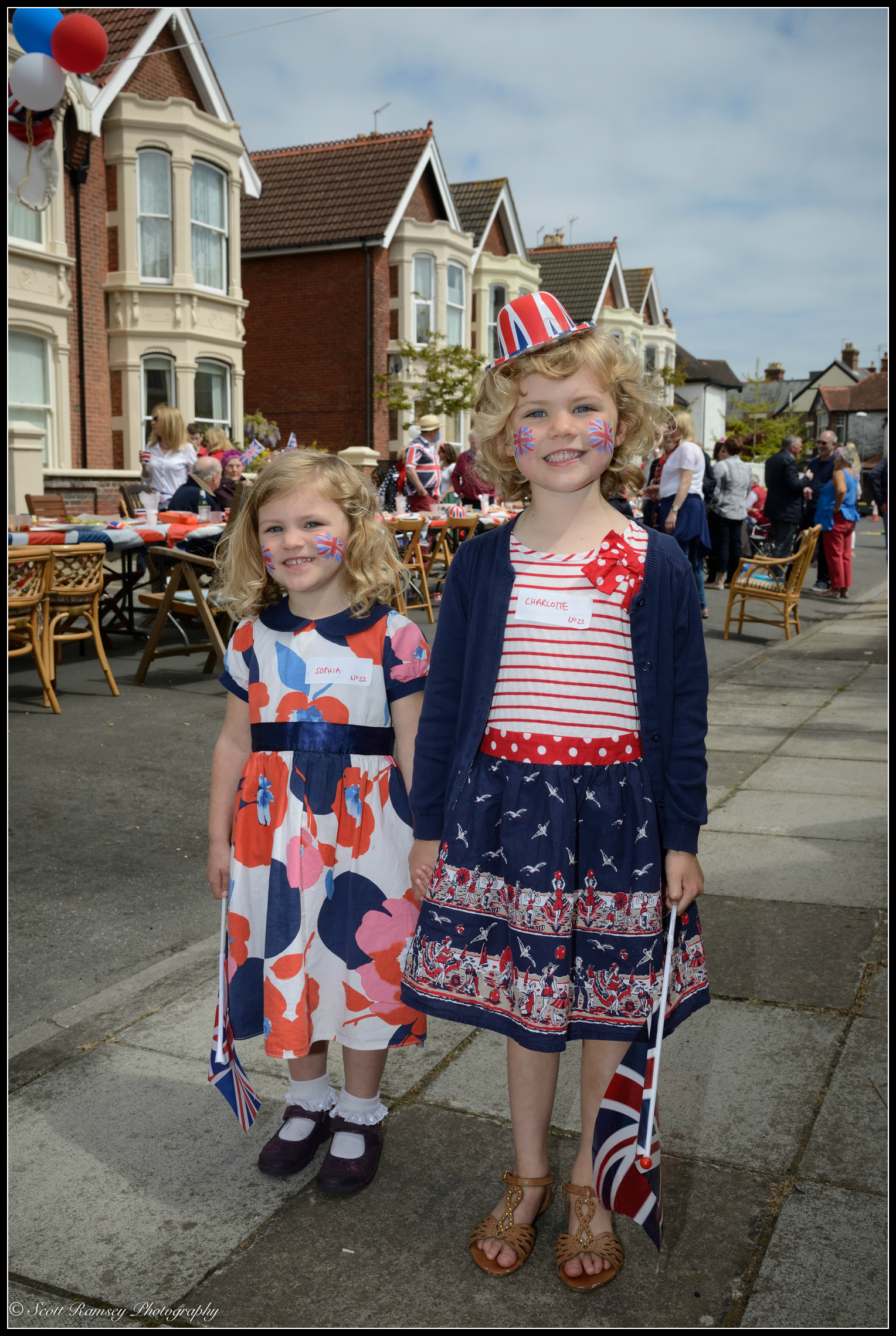 With painted faces, flagsand wearing their party dresses two girls pose for a photo during the VE Day 70th anniversary street party in Southsea, Portsmouth, UK. © Scott Ramsey Photography.
