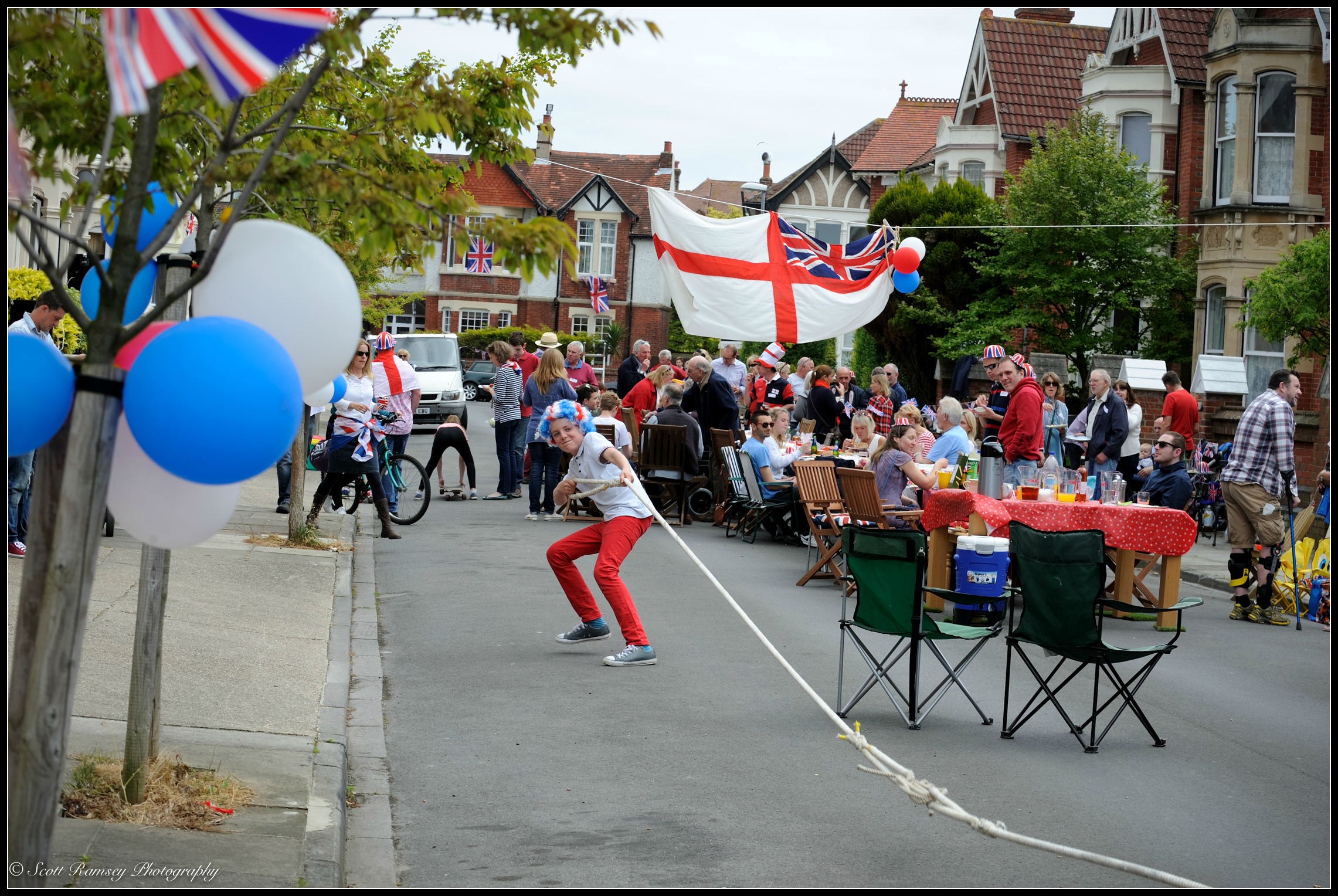 As residents enjoy the street party a boy wearing a colourful wig pulls on a large rope during a tug of war match. The community gathered together and organised aVE Day 70th anniversary street party in their road, Nettlecombe Avenue, Southsea, Portsmouth, UK. © Scott Ramsey Photography.
