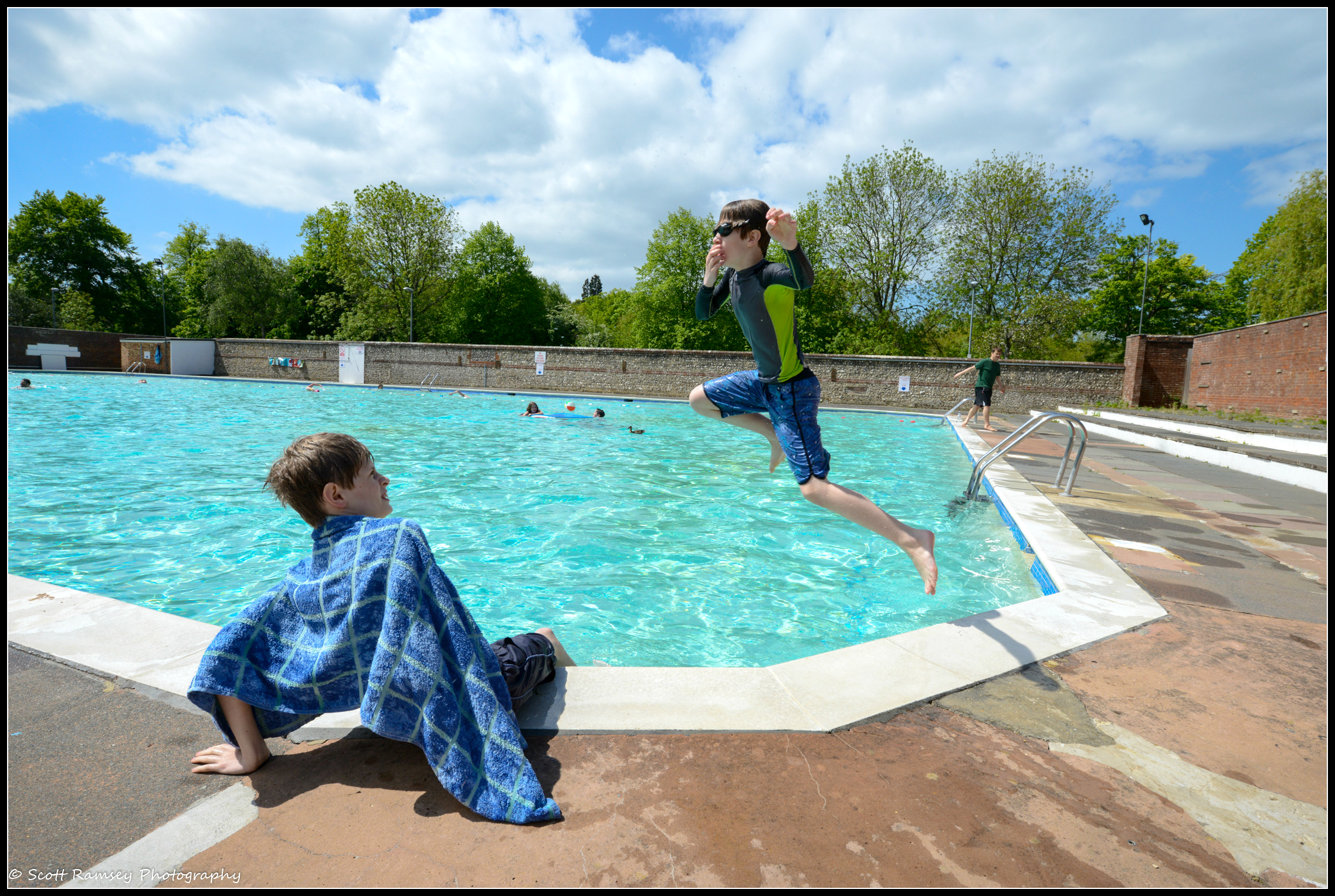 Watched by his friend a young boy holds his nose as he jumps into the swimming pool at Pells Pool in Lewes. © Scott Ramsey Photography