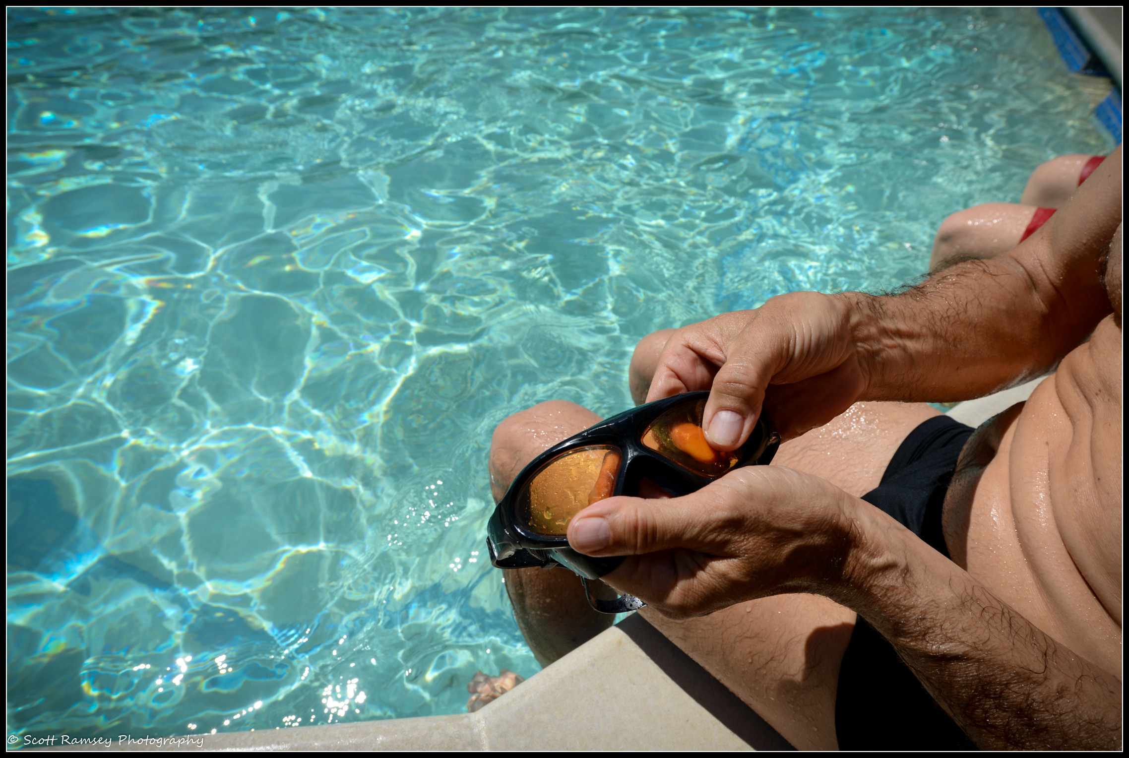 Tristan ,who has been swimming at the pool for 7 years, cleans his swimming goggles before his swim at Pells Pool in Lewes © Scott Ramsey Photography