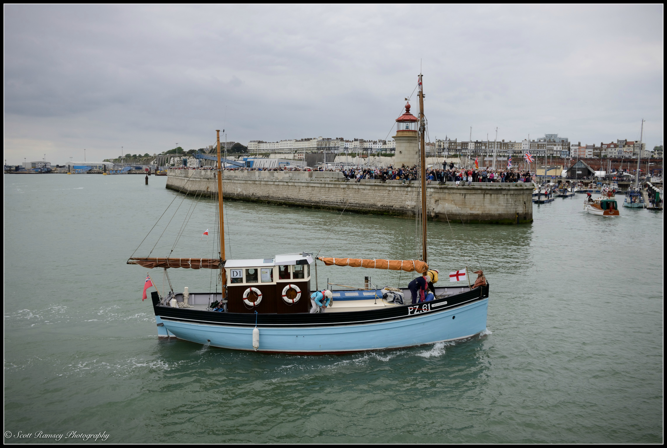 Spectators wave flags and cheer as The Maid Marion, a 1925 Cornish lugger and one of the original Dunkirk Little Ships, returns to the Royal Harbour Marina Ramsgate during a weekend of events to commemorate the 75th anniversary of Operation Dynamo. ©Scott Ramsey Photography