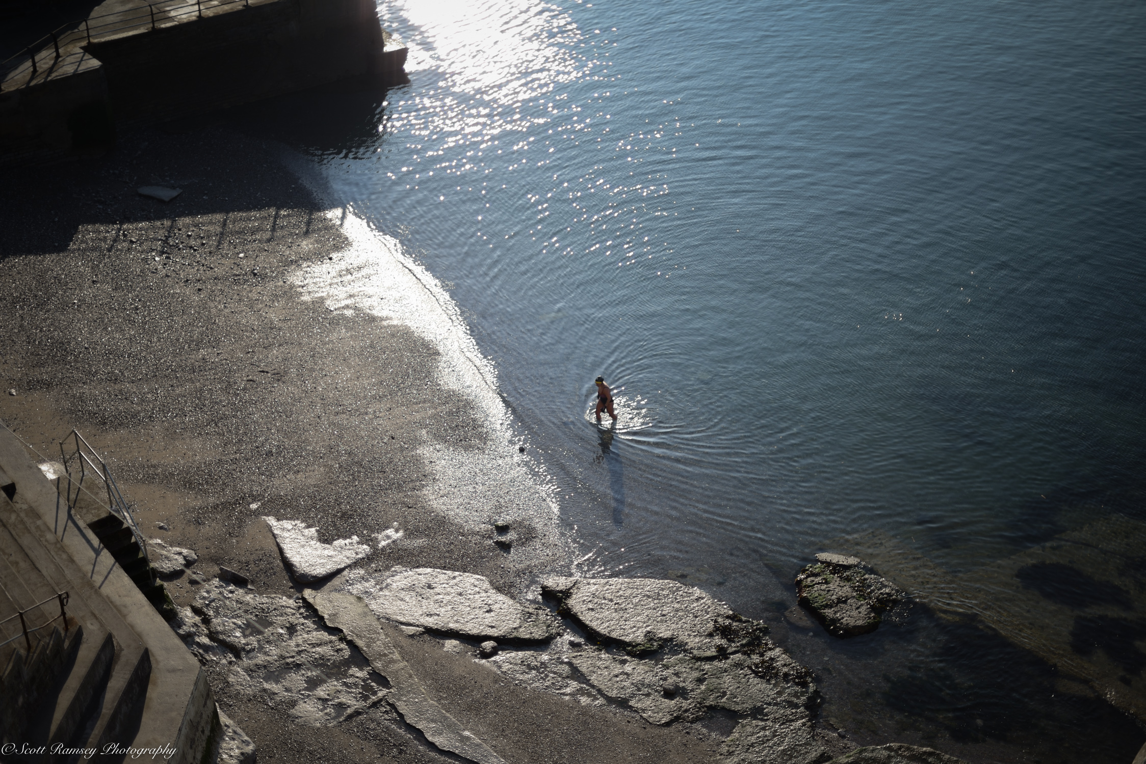 A swimmer emerges from the sea on to the beach at Plymouth Hoe, Devon. Photo © Scott Ramsey