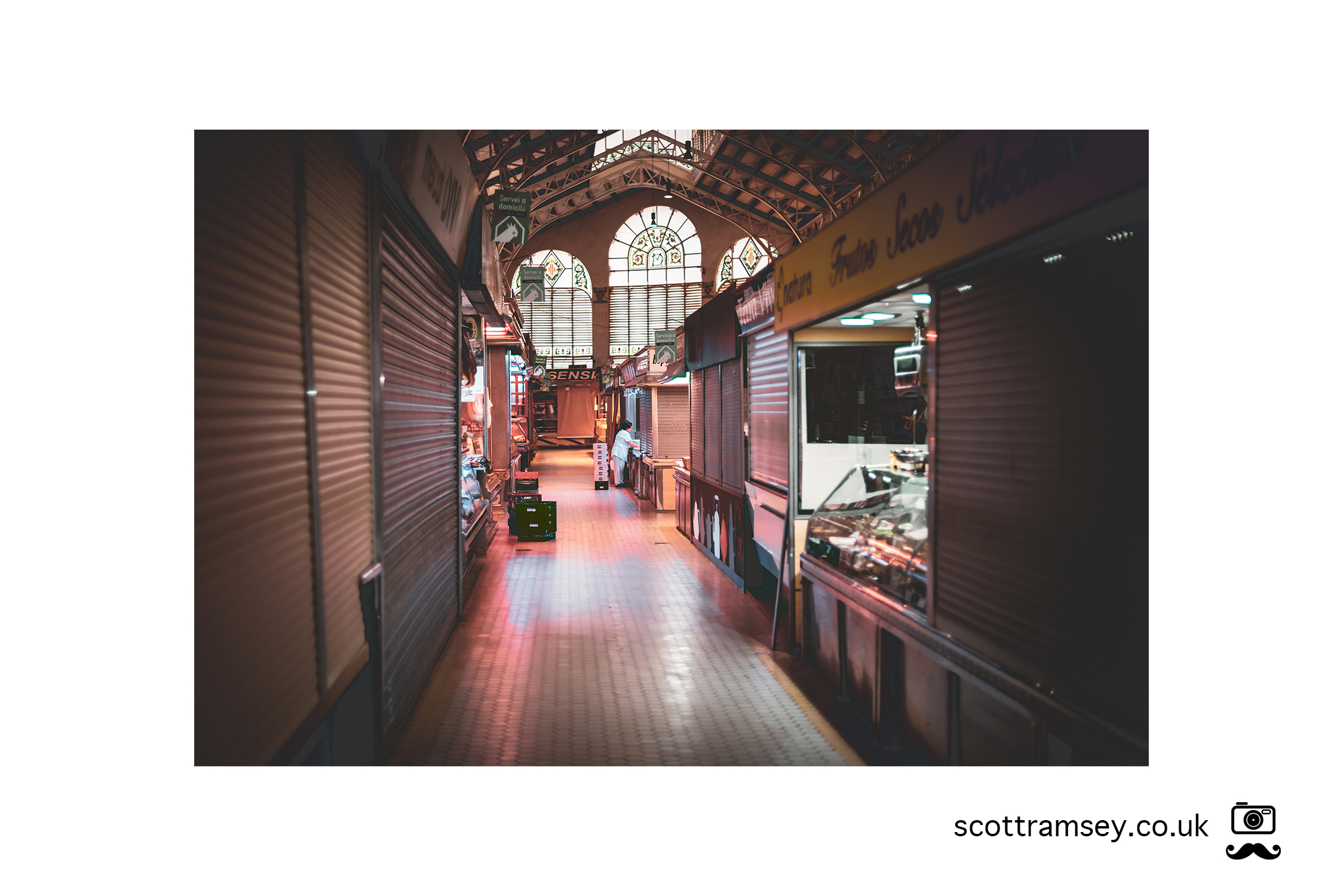 Early morning at The Central Market in Valencia, Spain and a woman prepares her market stall before customers arrive. Photo © Scott Ramsey