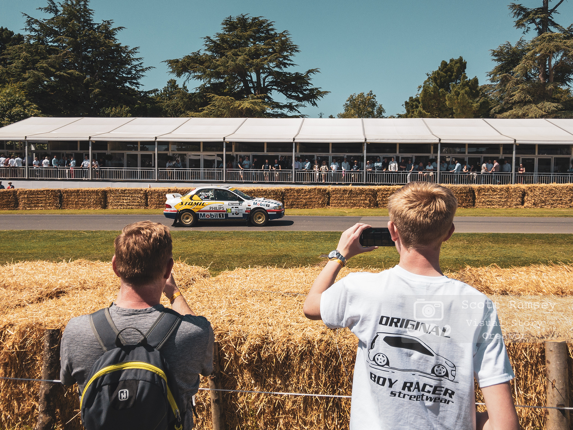 UK Professional iPhone Photographer Scott Ramsey Documents The Goodwood Festival Of Speed. In Photo - Boy Racer's photograph a car at the event in Chichester, West Sussex. © Scott Ramsey - Photographer & Visual Content Creator.