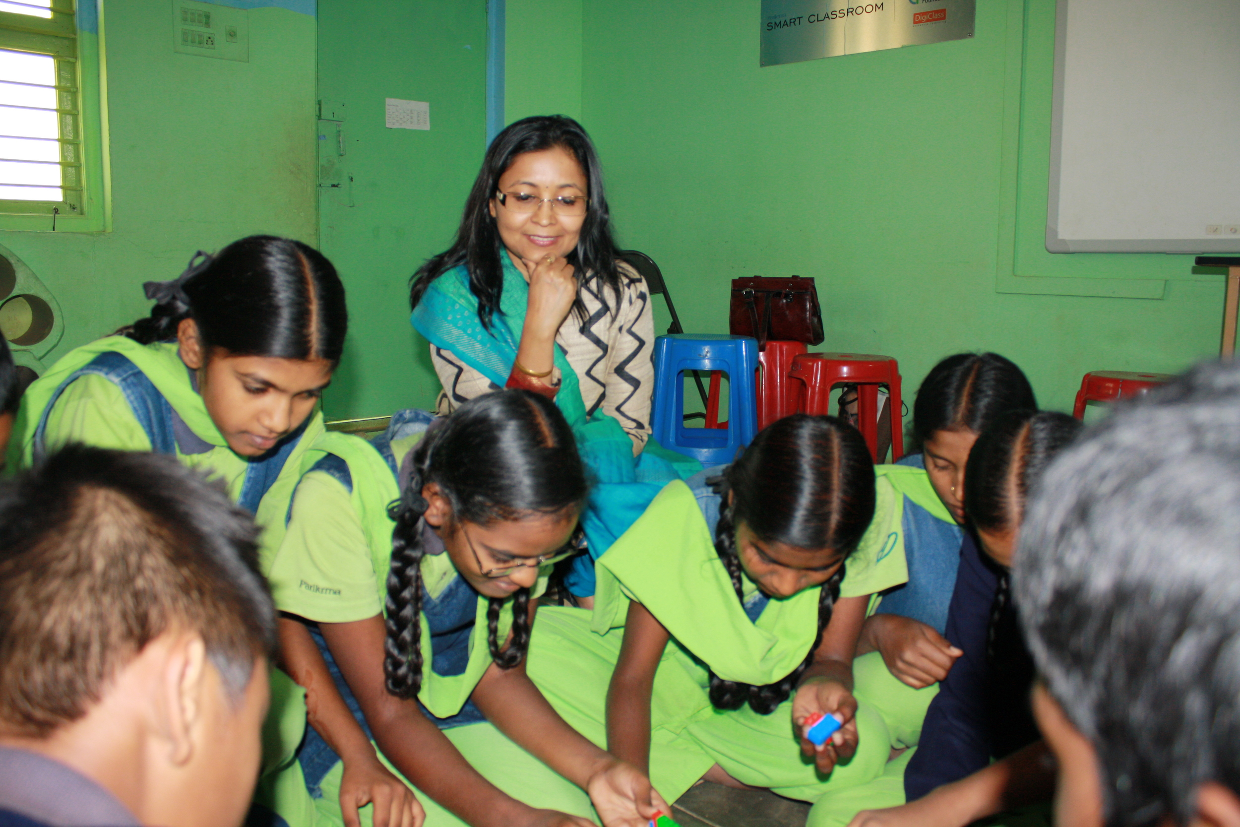 Chandana watches over the girls as they do their experiment