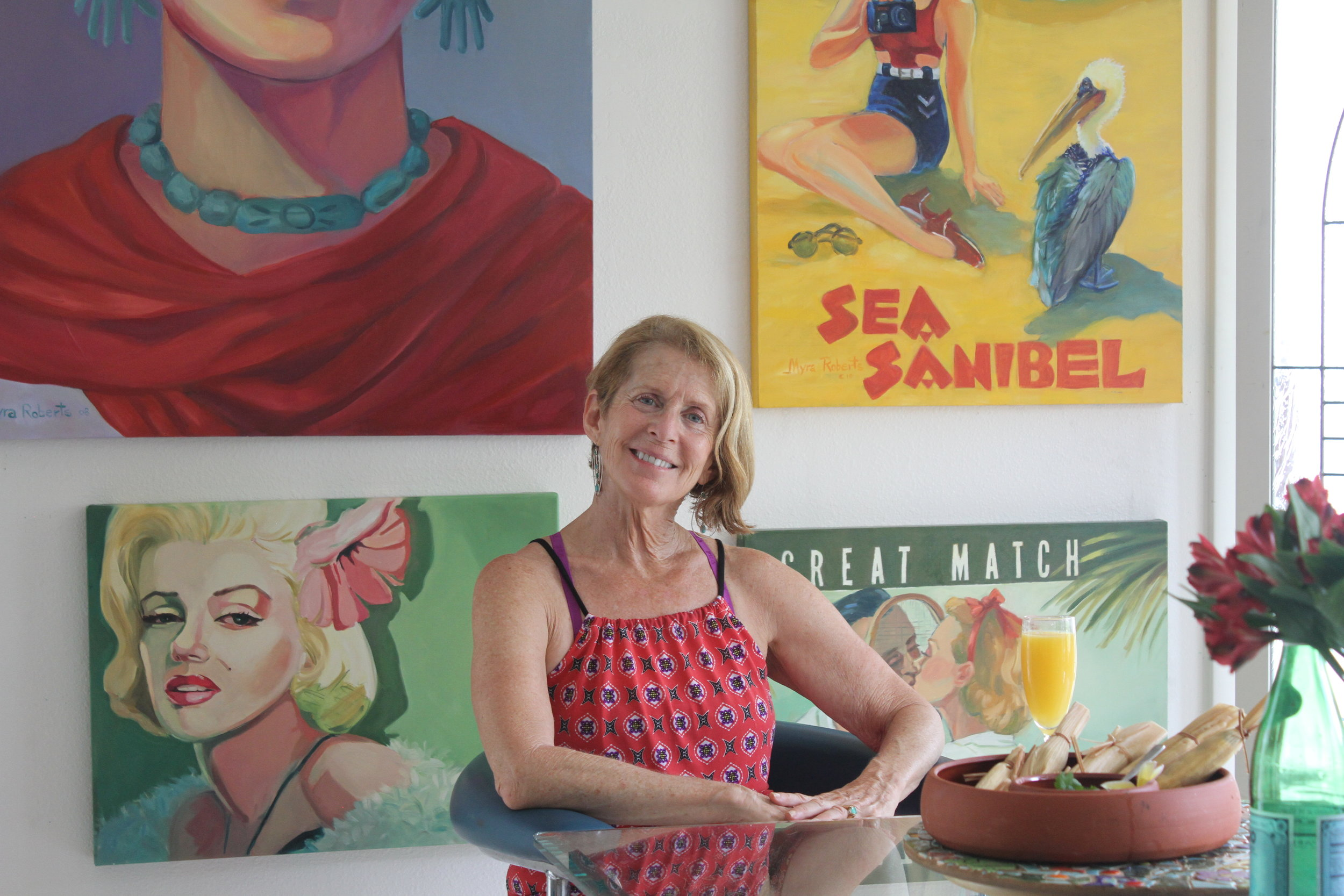 Myra Roberts in her dining room surrounded by some of her artwork.