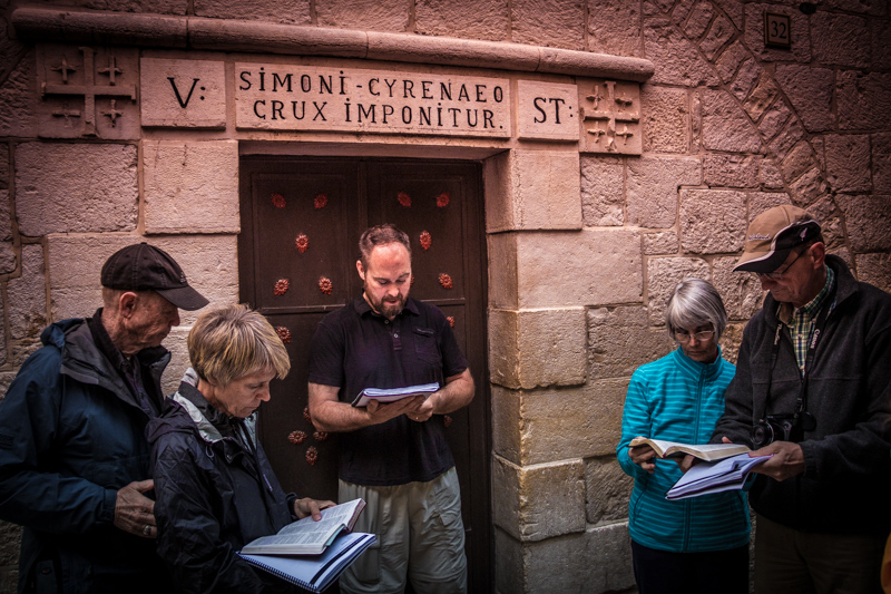 Walking the traditional Via Dolorosa, the Way of Jesus' Suffering, and reflecting at Station Five marking Simon of Cyrene being compelling to carry Jesus' cross.