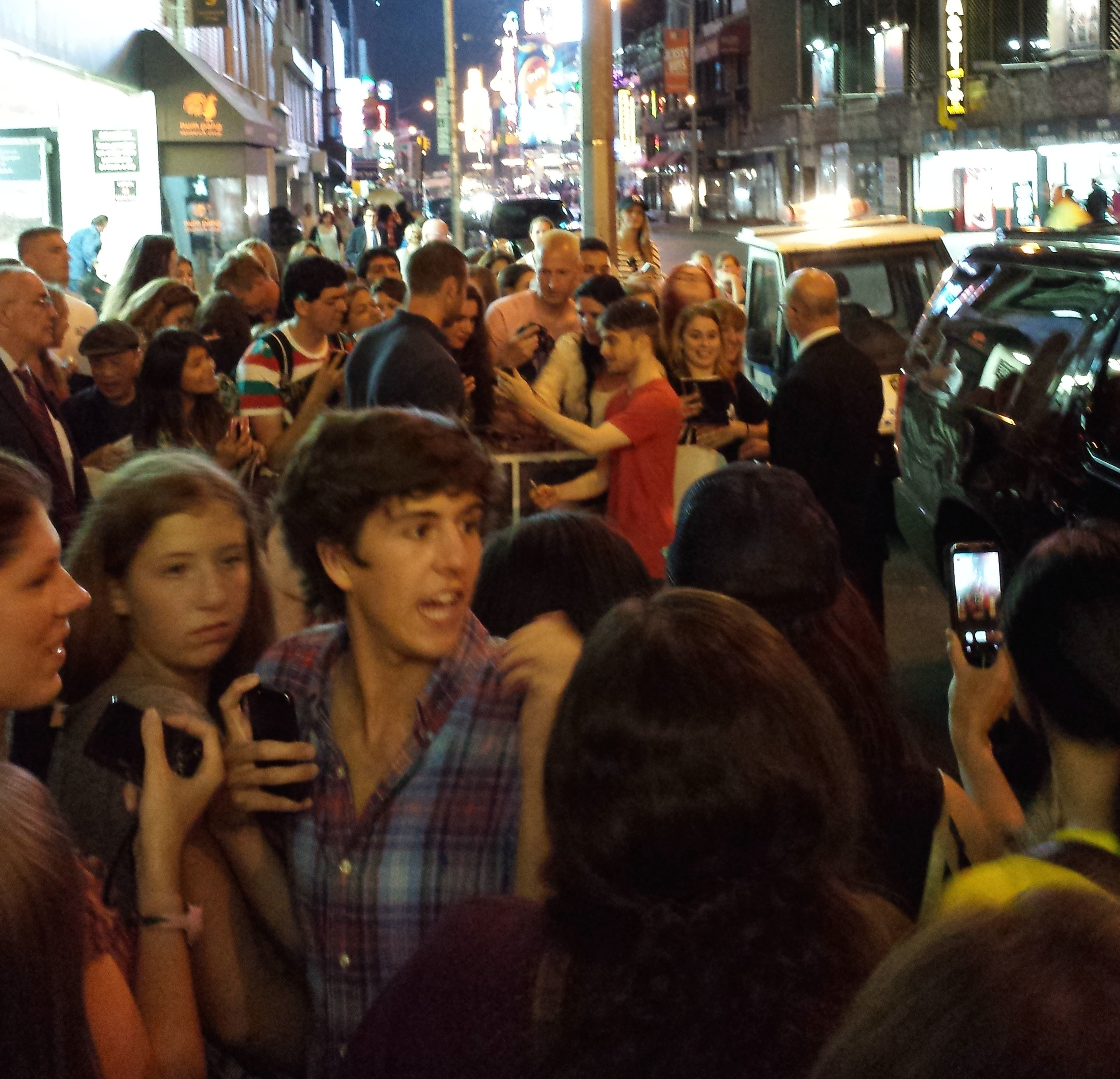 Daniel Radcliffe (Harry Potter, red shirt) takes photos with fans outside of his Broadway show   The Cripple of Inishmaan  . Two police officers stand by. He was doing this when we happened by, and continued as we walked past.