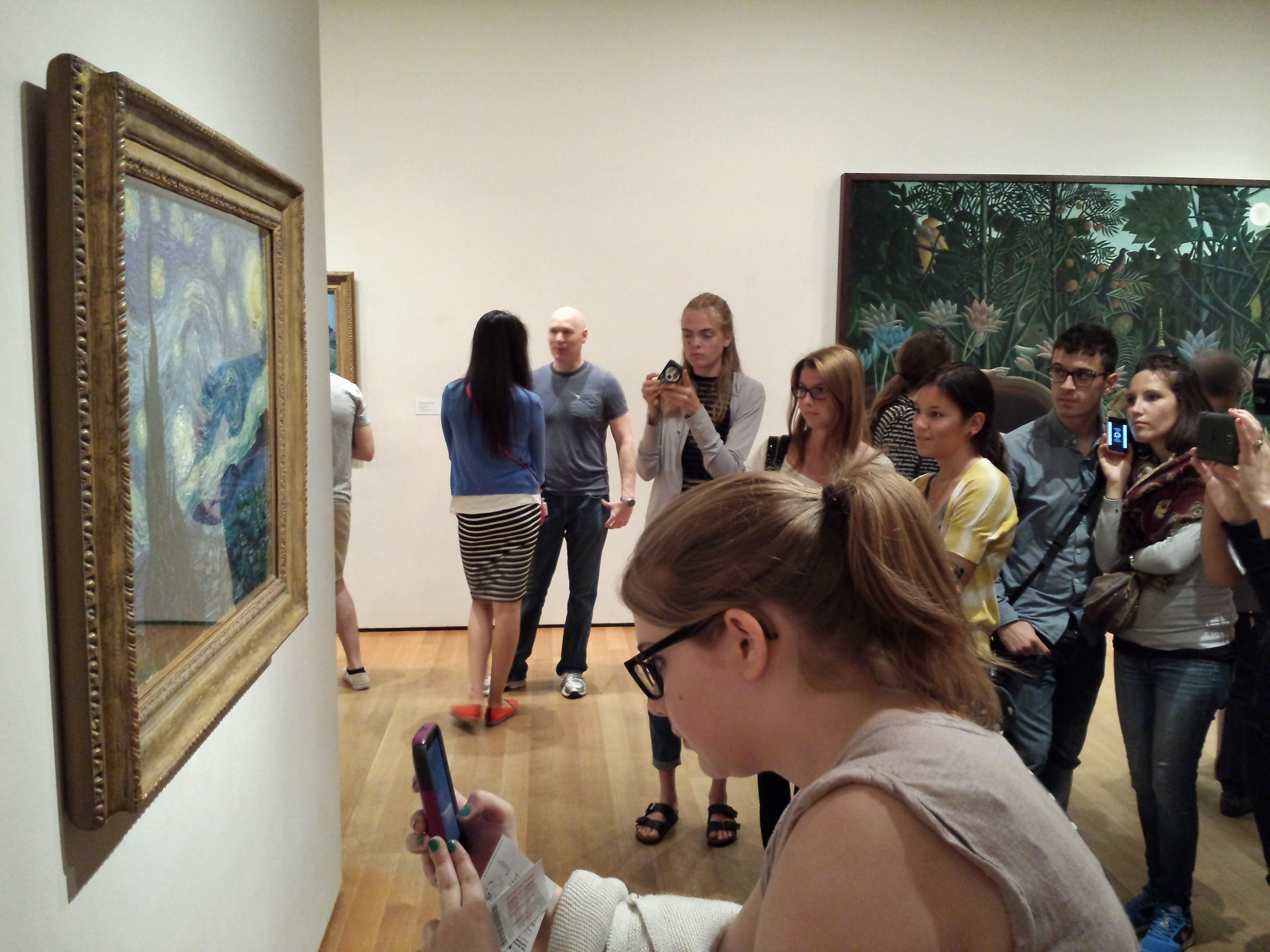 """Crowds hovered around famous pieces. Here Van Gogh's """"The Starry Night"""". I took photos, too. Behind is """"The Dream"""" by Henri Rosseau"""