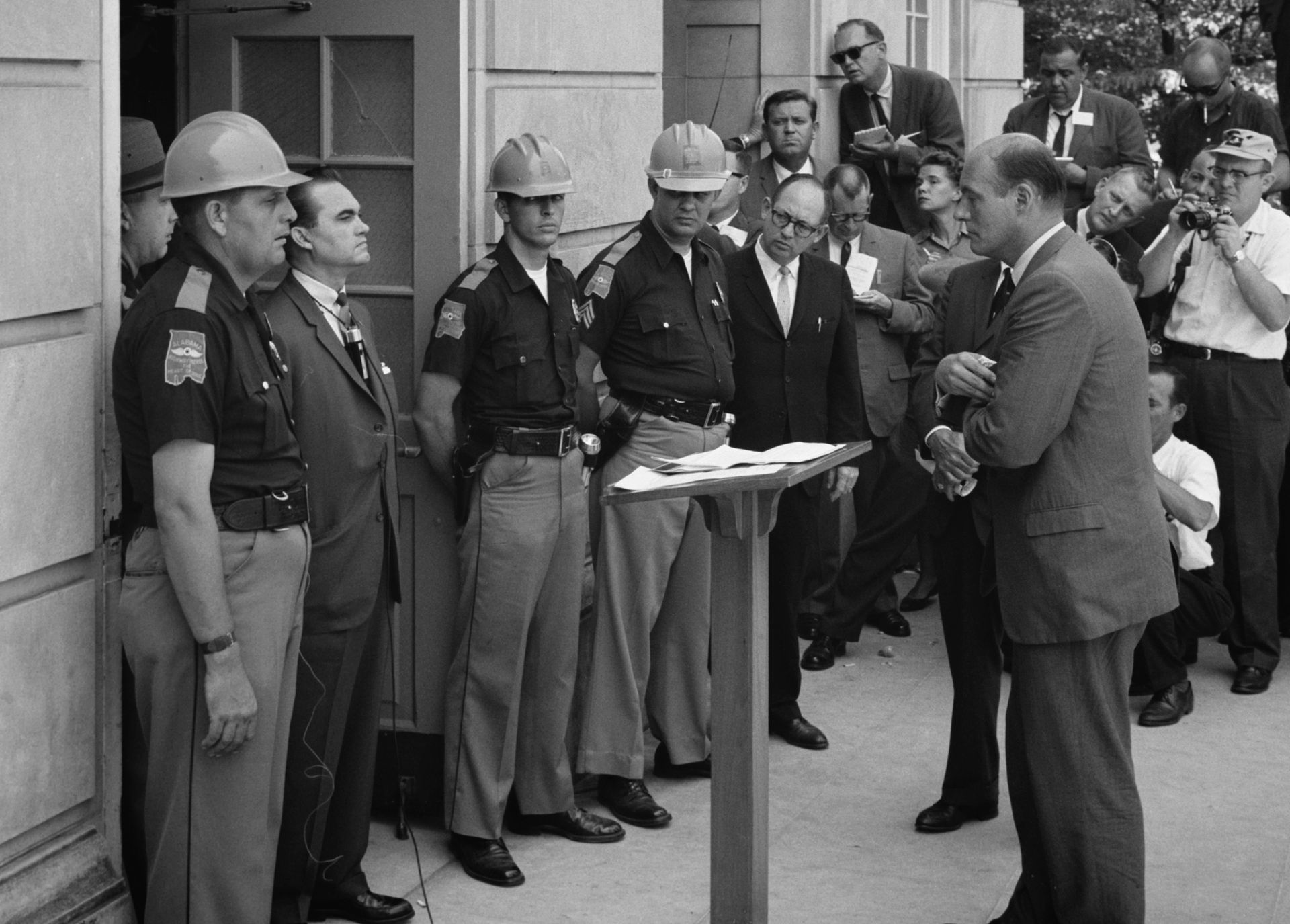 "Gov. George Wallace (left, in a suit next to the mouth-breather), the Ur-Nancy Davis, ceremonially blocking black students from entering Foster Auditorium at the University of Alabama. ""Segregation now, segregation tomorrow, segregation forever."" Asshole."