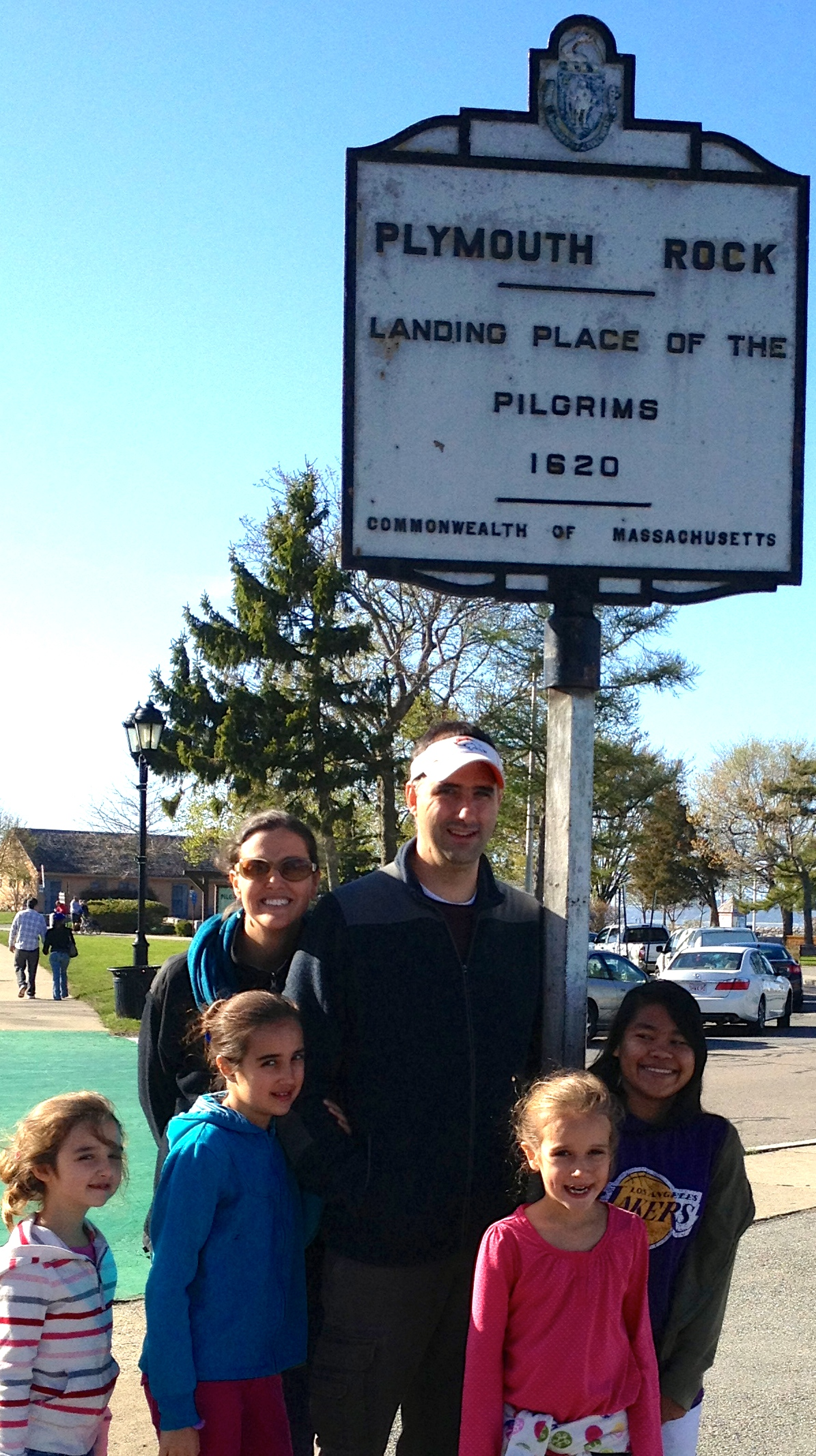 The fam standing in front of the sign marking Plymouth Rock.