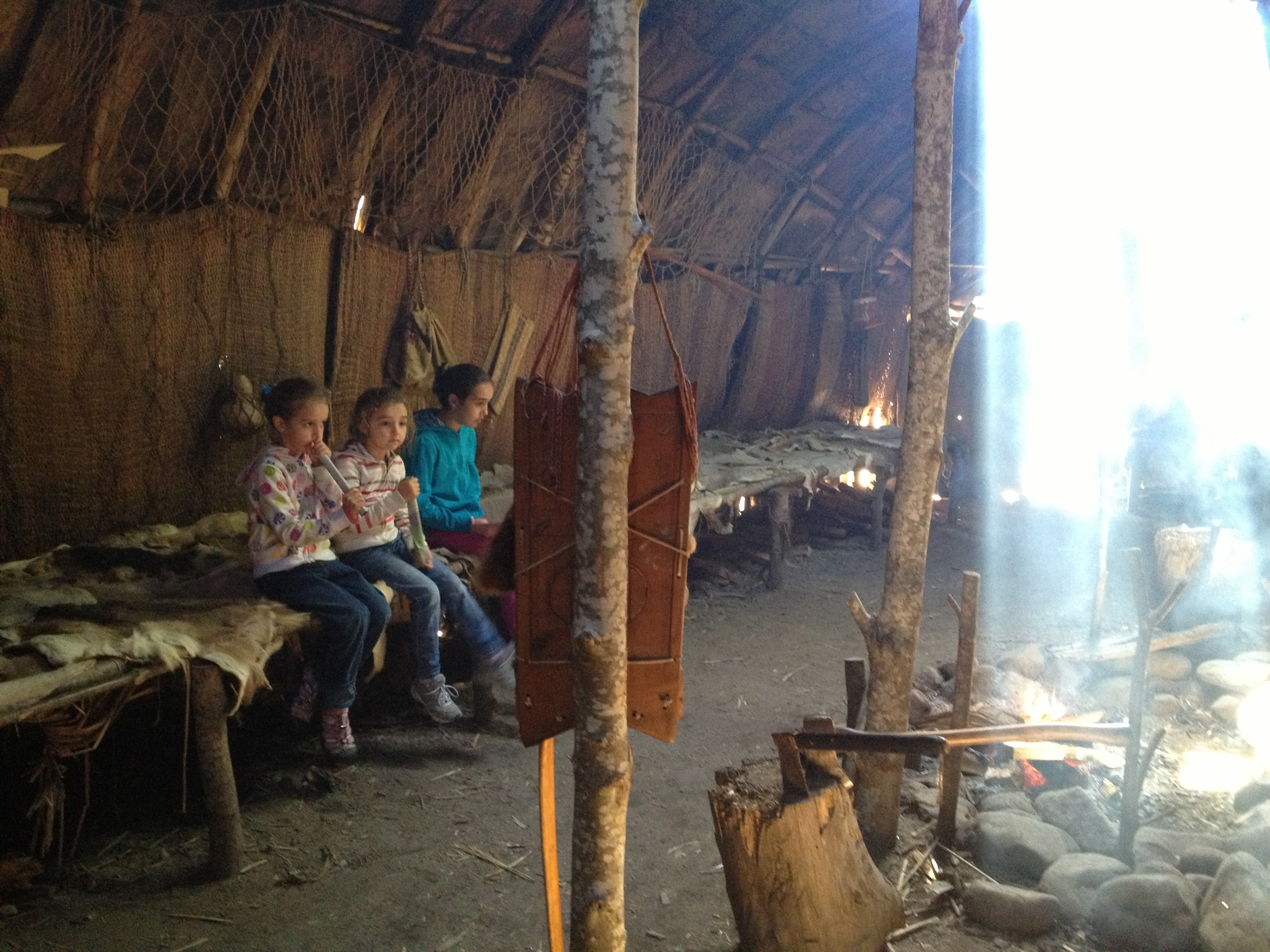 The girls inside a Wampanoag home learning from a Wampanoag descendent of their way of life in the 1600s.