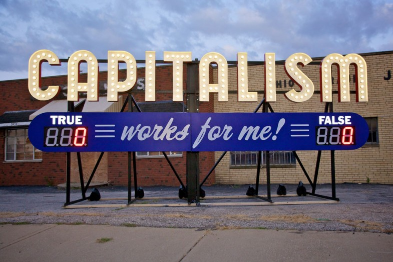 """""""capitalism works for me! true/false"""" by steve lambert, 2011. 9 ft x 20 ft x 7 ft, aluminum and electrical"""