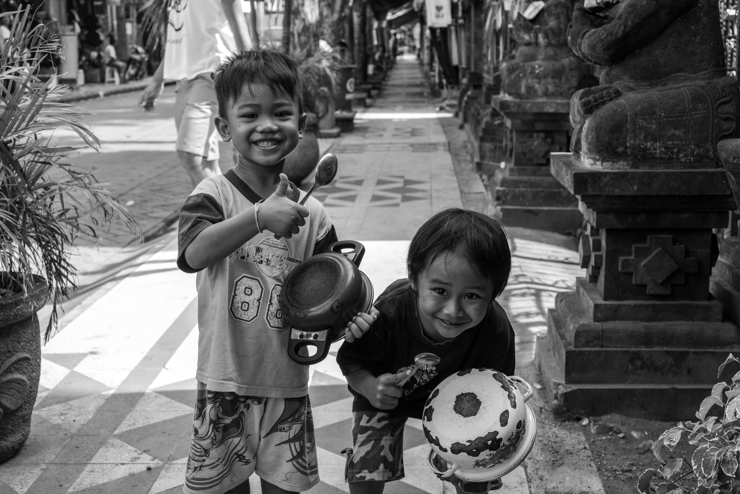 Very happy local kids playing pots and pans in Kuta.