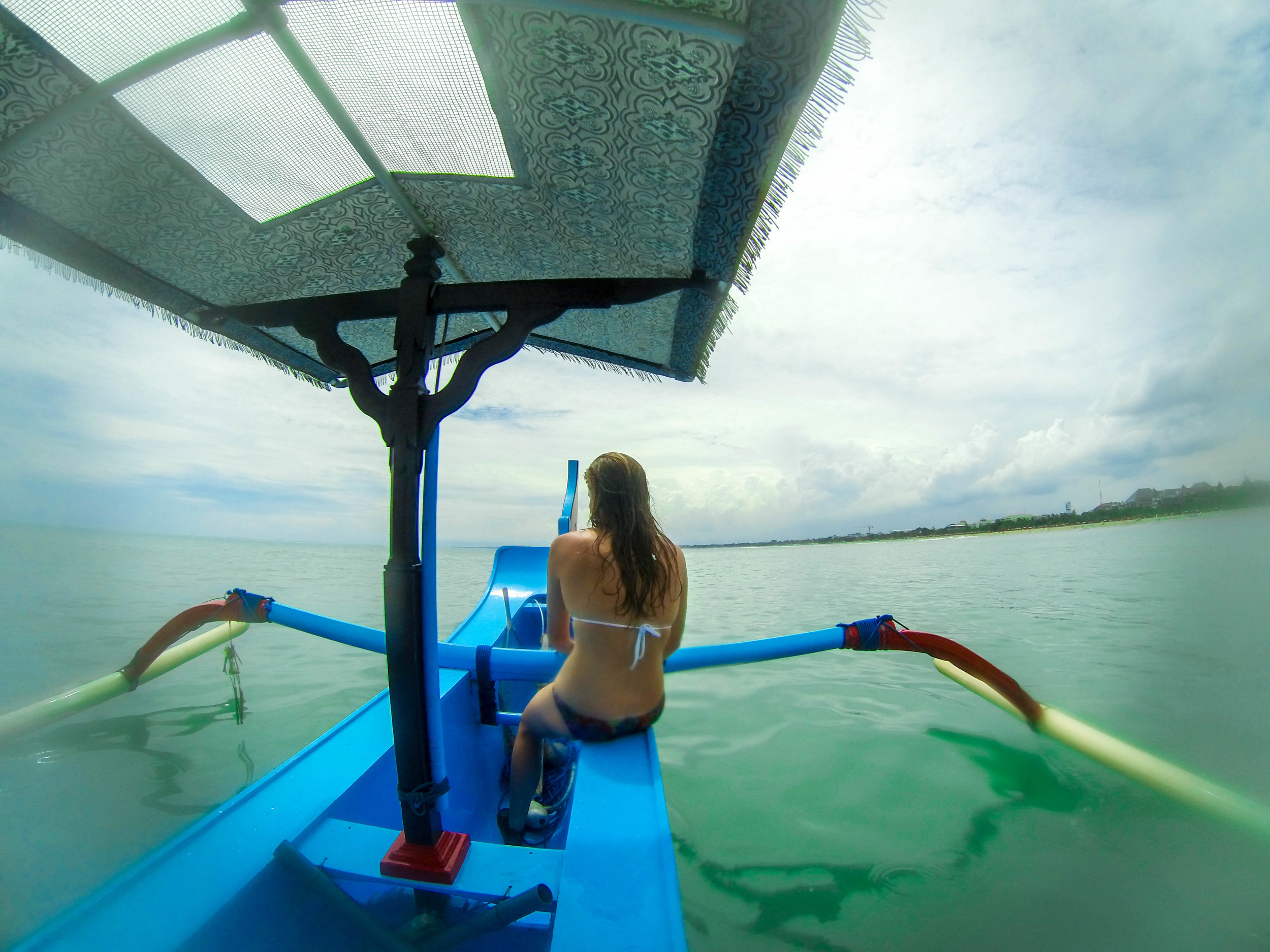Taking a boat out to surf Airports, which is a reef break just near Kuta beach.