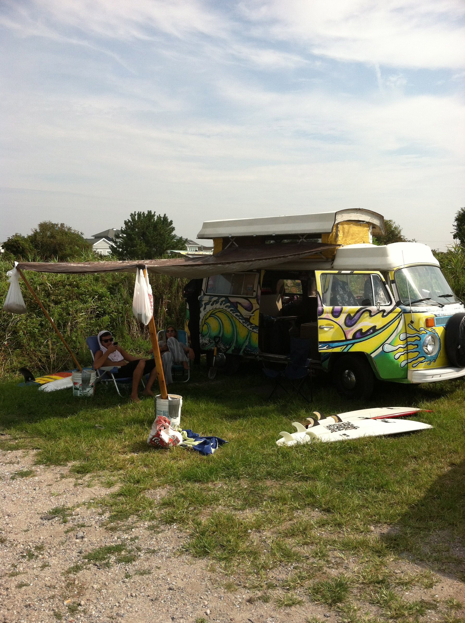 """Thank you for the inspirational photo and words@crosstepculture and @saltroots """"I captured this image last summer at Lido Beach, New York. We had just gotten out from our first surf of the day and the sun was already beating down on us as we walked back to """"Rivi"""", my 1977 Volkswagen Bus. After an hour or so in the hot sun, we decided to rig up an awning to provide some refuge from the heat. Michelle and I rallied together a few of our friends and scoured the beach for anything we could use to pitch the tarp we had on hand. After about twenty minutes we had collected two cracked spackle buckets, five zip-ties, three plastic bags, a piece of rope, and old lobster trap, and two pieces of wood. Common beach trash was ingeniously re-porposed by our group of friends and built a pretty solid awning that even withstood a brief thunderstorm later that afternoon. We were all incredibly stoked with our creation, and still talk about it to this day. It was a great experience and a gorgeous day of fun surf, good friends, and good memories. Can't ask for much more than that in life""""."""