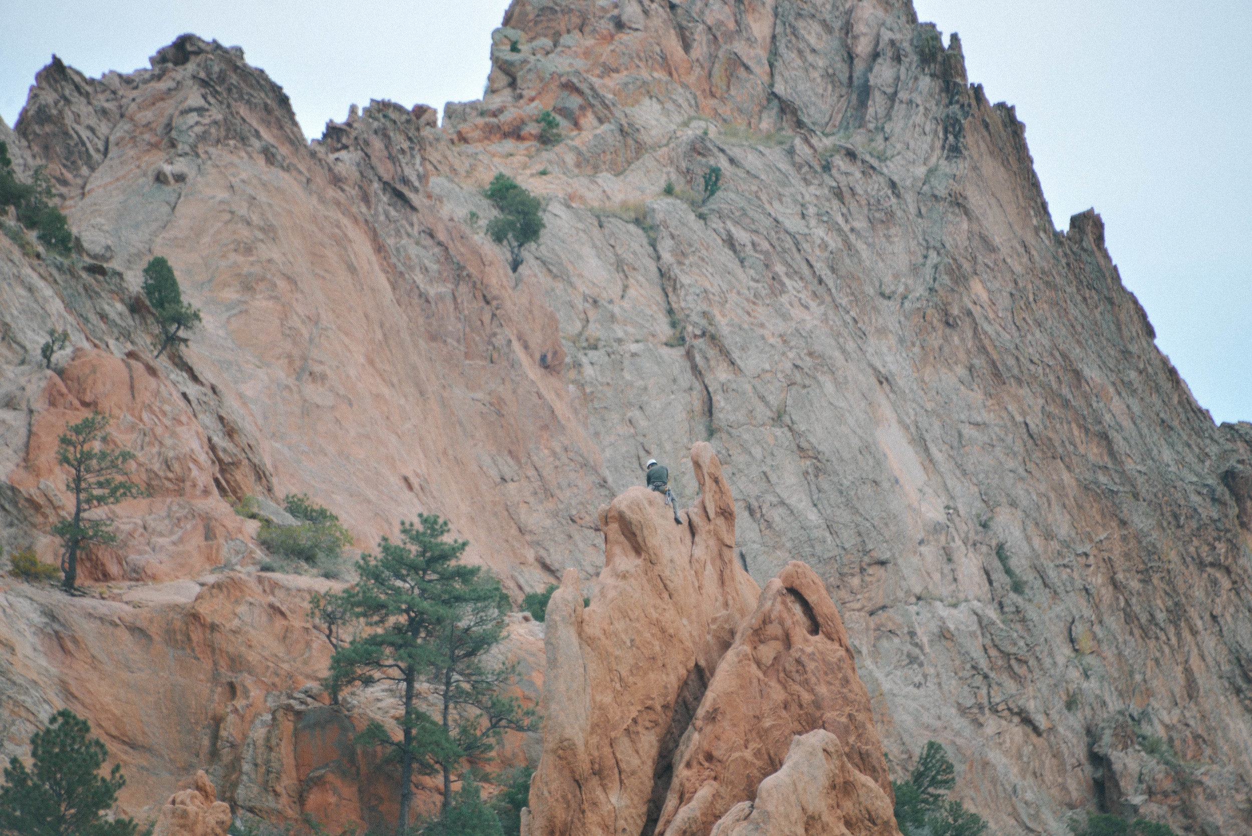 Rock climber sitting high.