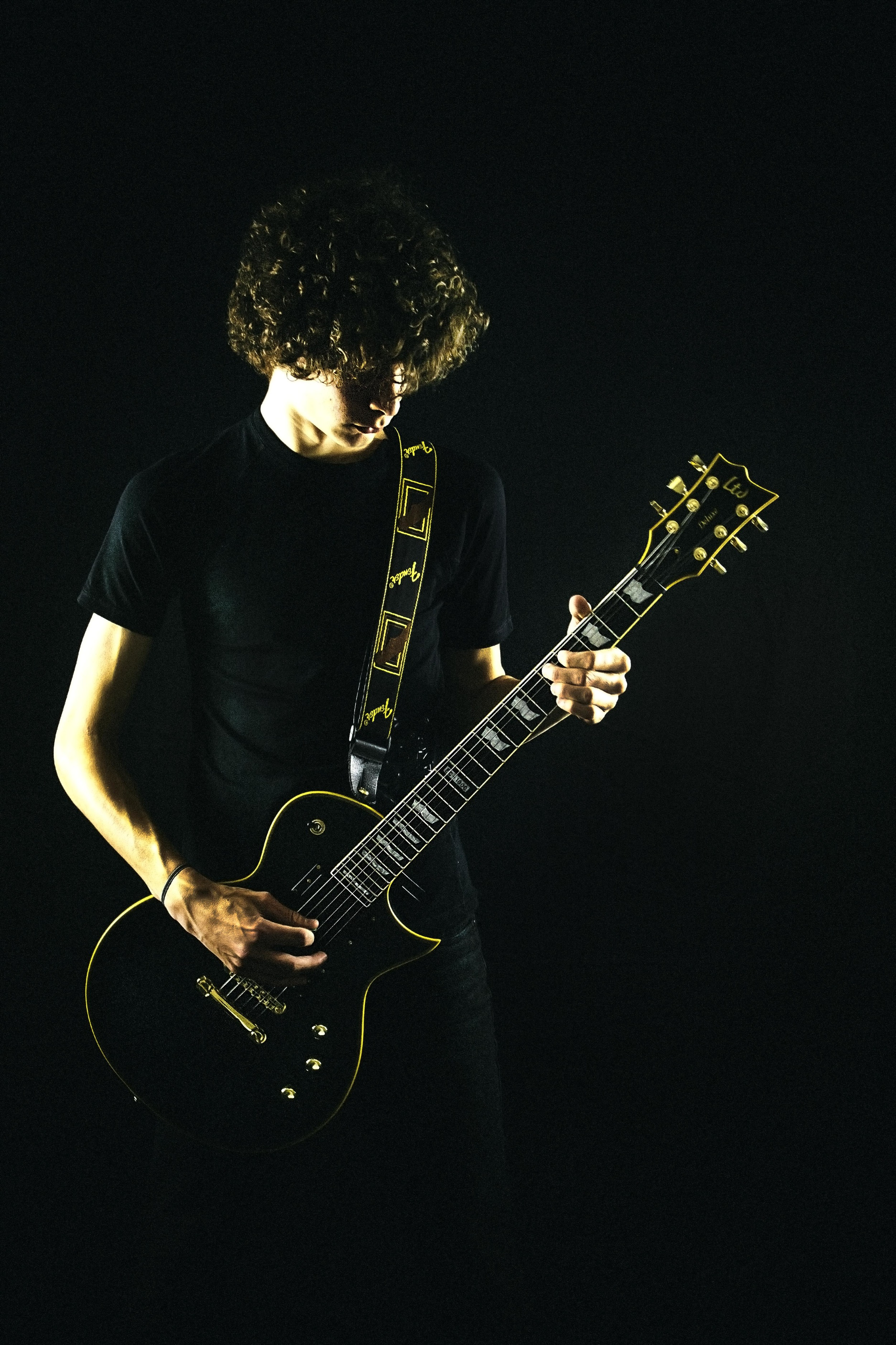 A 2 light setup in the studio with a black backdrop to catch highlights and to lighten the guitar.