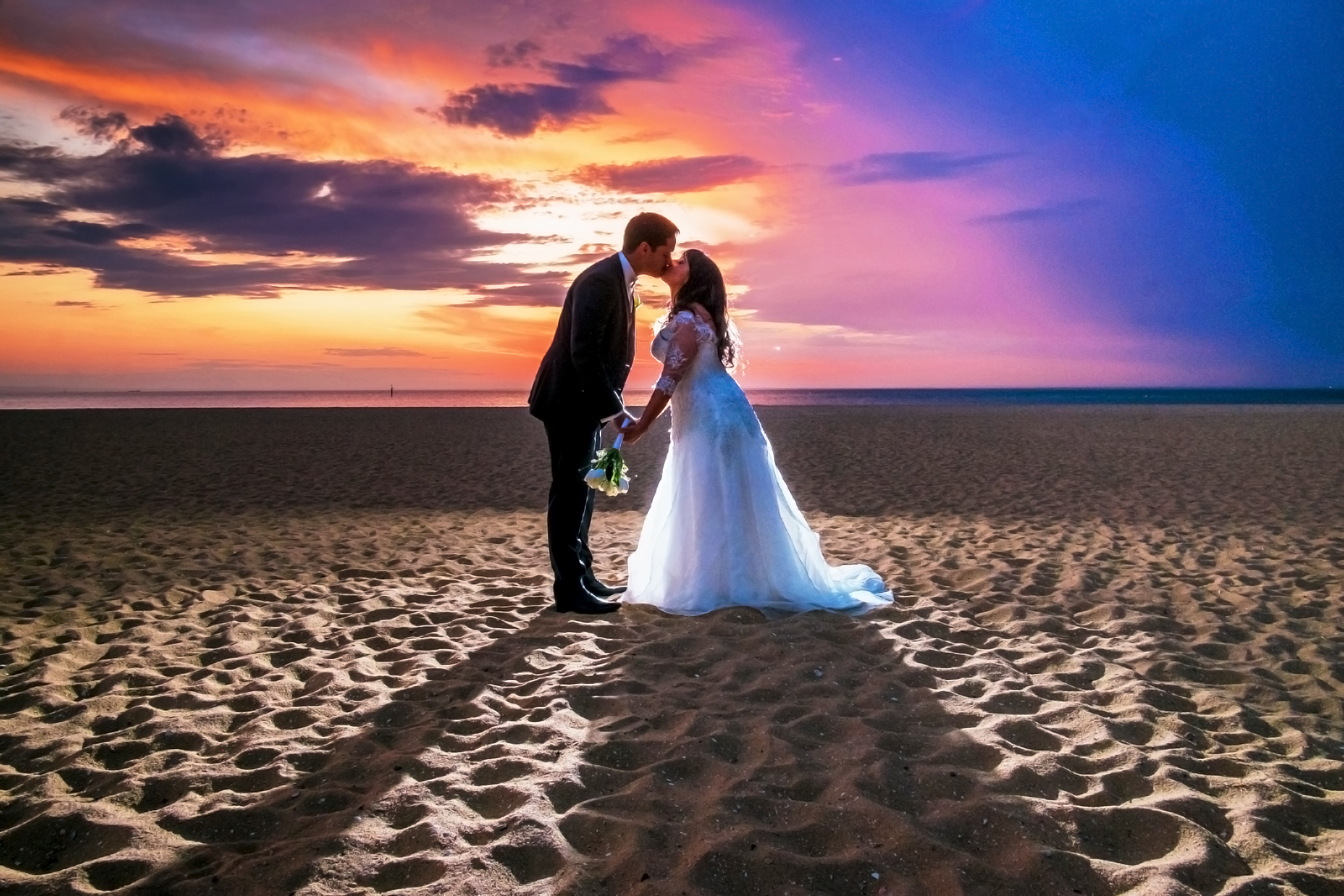 Brighton-beach-sunset-bride-and-groom-kissing-on-sand.jpeg