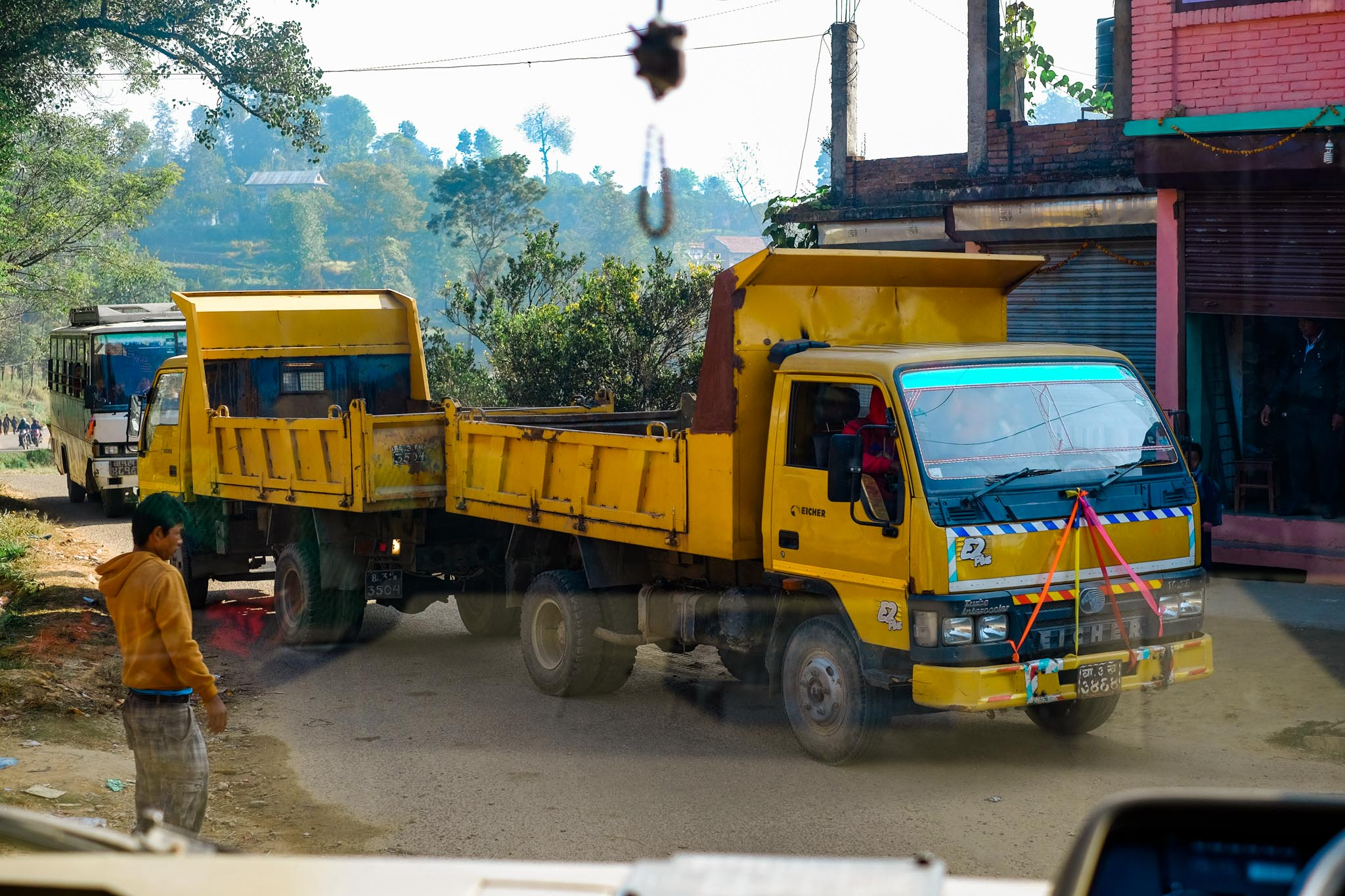 3/4 of the way to the school the road was blocked by these two tip trucks. One had to push the other down the hill to jump start it and eventually after 5 minutes the road was free again.