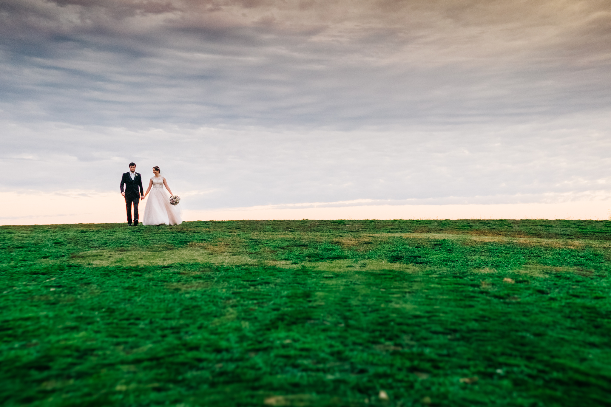 Bendigo_wedding-Amazing-Winery-Wedding-Photography-bride_and_groom-strolling in-open-field-on-a-hill.jpeg