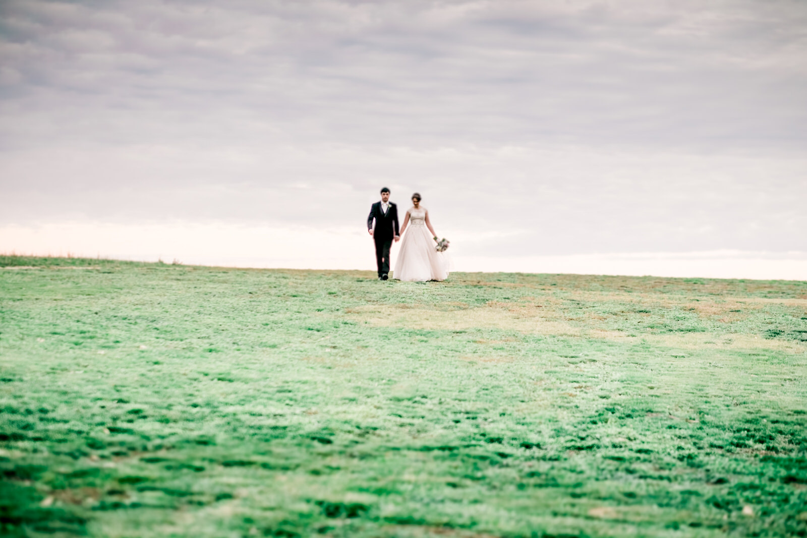 Bride-and-groom-on-a-hill-in-country-victoria-winery-walking-hand-in-hand-in-a-romantic-setting.