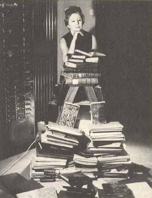 Anais Nin poses with her life's work of journals.