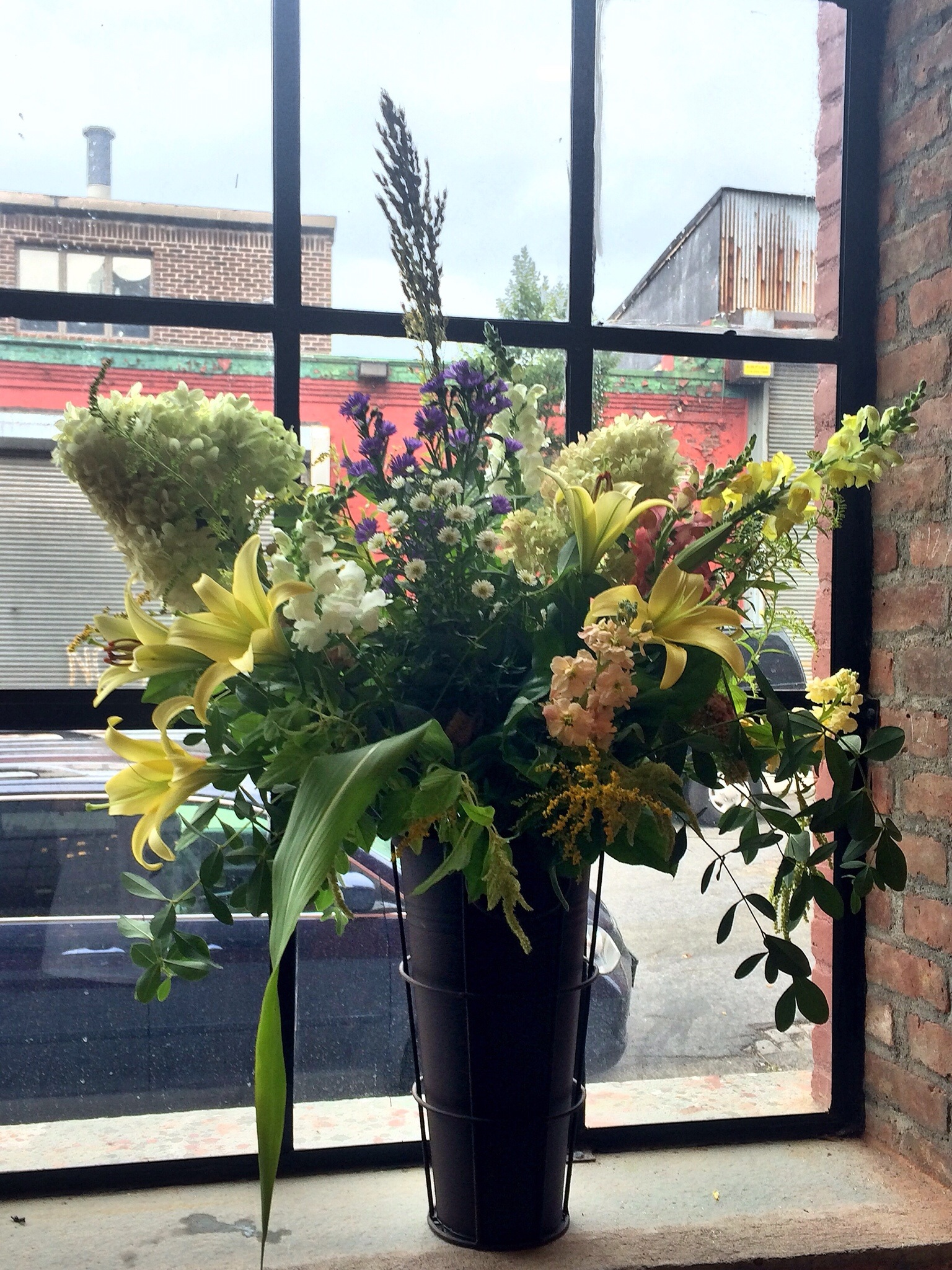 Three galvanized vessels with wrought iron patina were a perfect choice for a fall harvest look of broom corn, hydrangea, and lilies in soft bronze colors in the stunning front window. Photo: KanKan Yu, Washington, D.C.