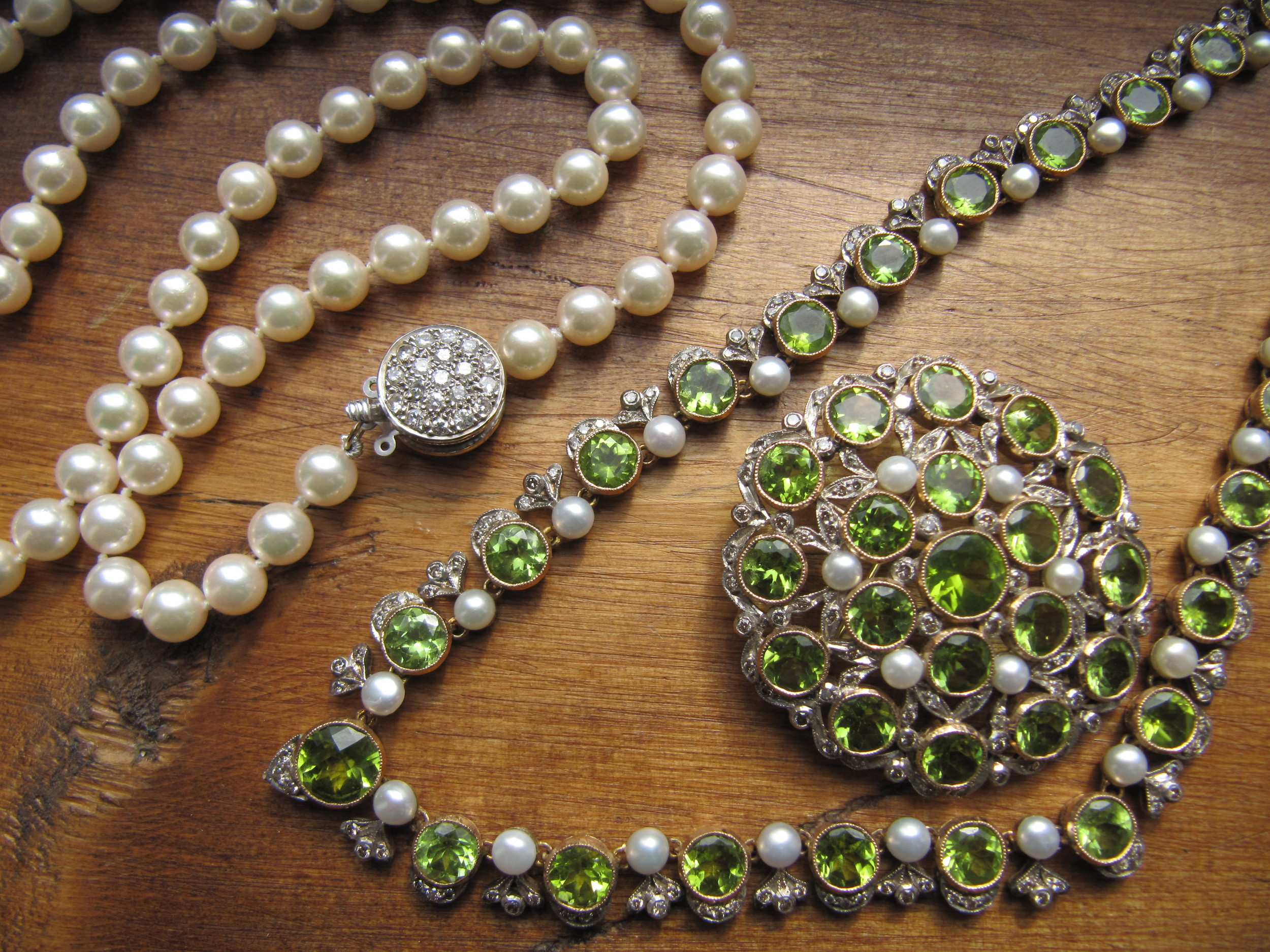 Pearl necklace with diamond clasp $1875 and an Edwardian era platinum on gold, peridot, pearl and diamond necklace with detachable pendant/broach $12,000 for the set, both available at Walton's.