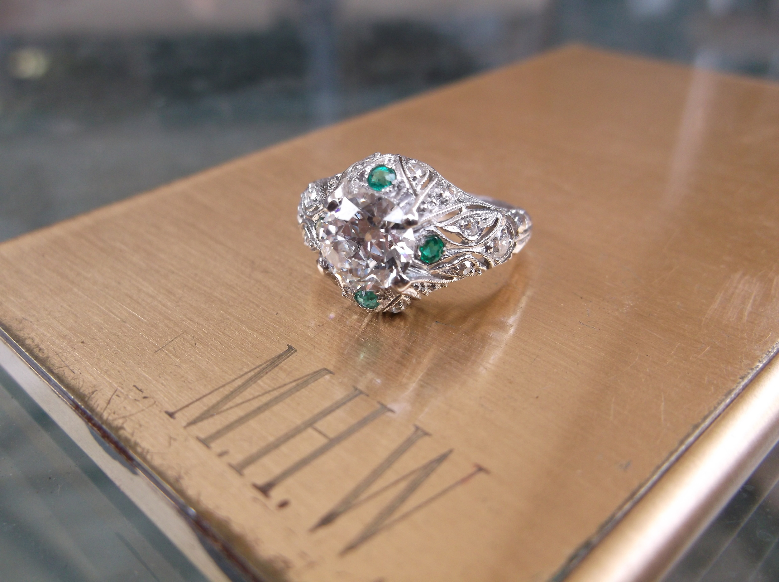 SOLD - Enchanting 1920's 1.04 carat diamond ring set in a platinum filigree setting with beautiful emerald details!