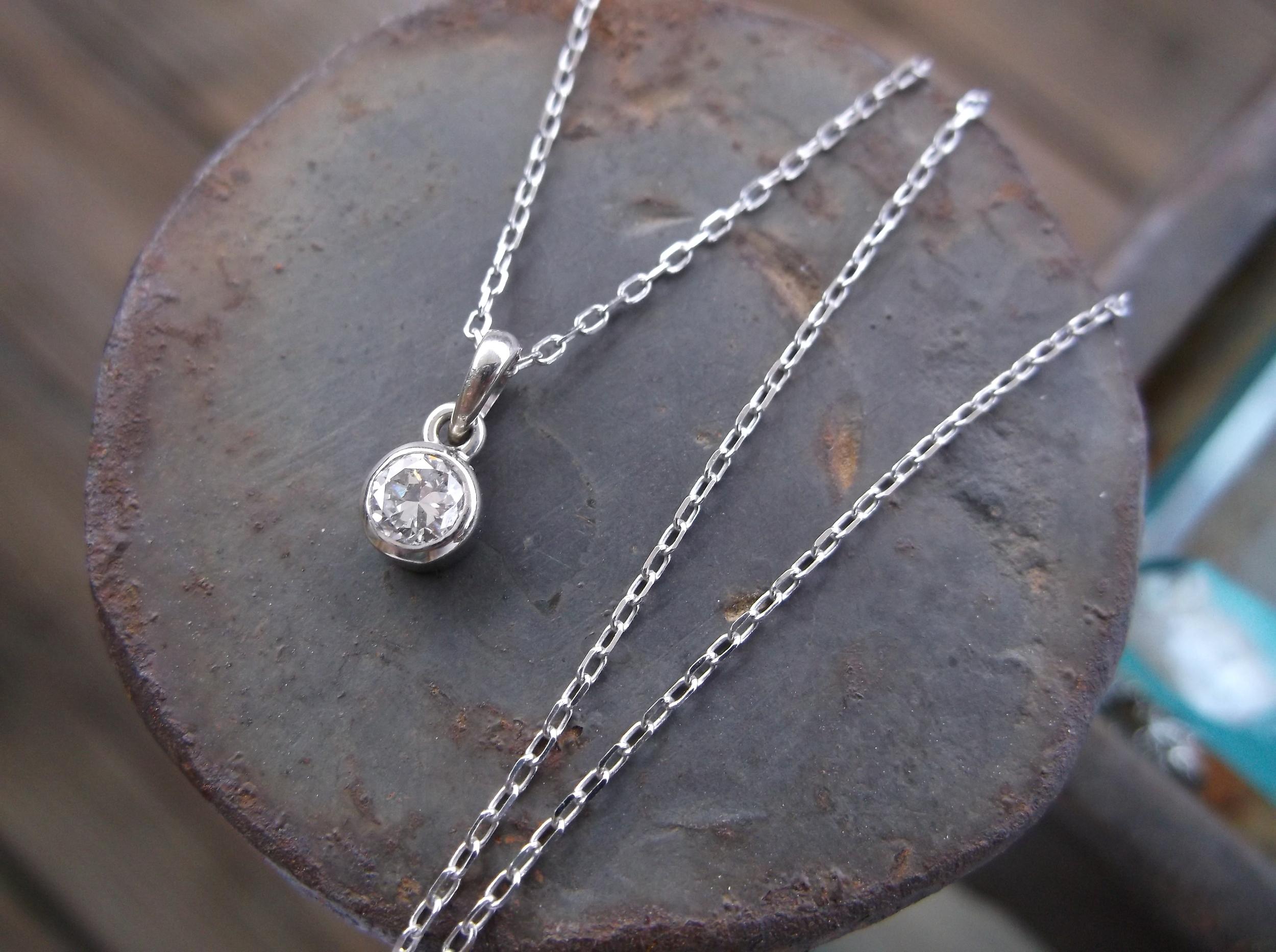 0.15 carat Old European cut diamond bezel set pendant in 14K white gold.