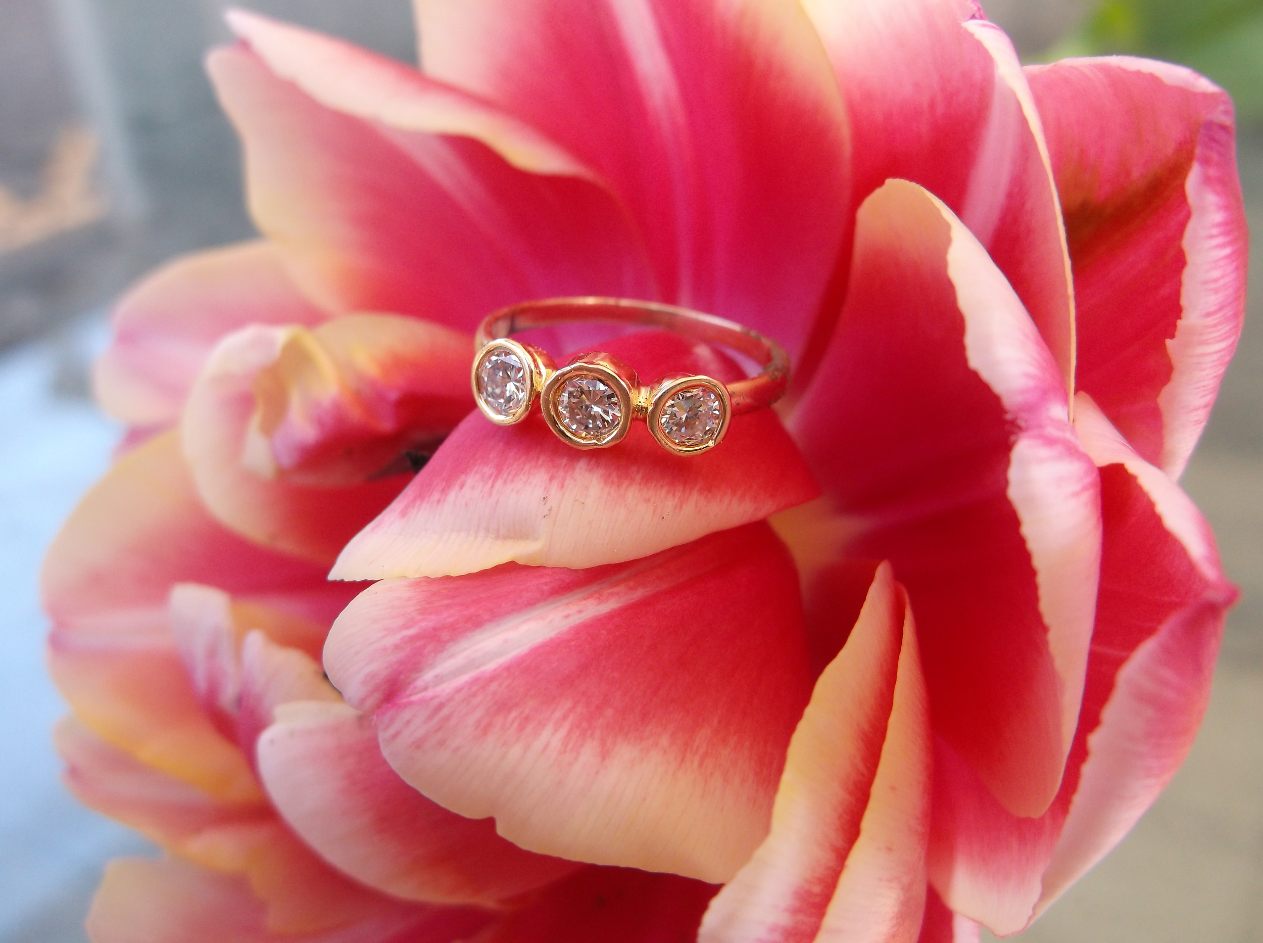SOLD - Dainty three stone diamond ring set in a 14K yellow gold bezel moutning with 0.30 carats total weight in diamonds.