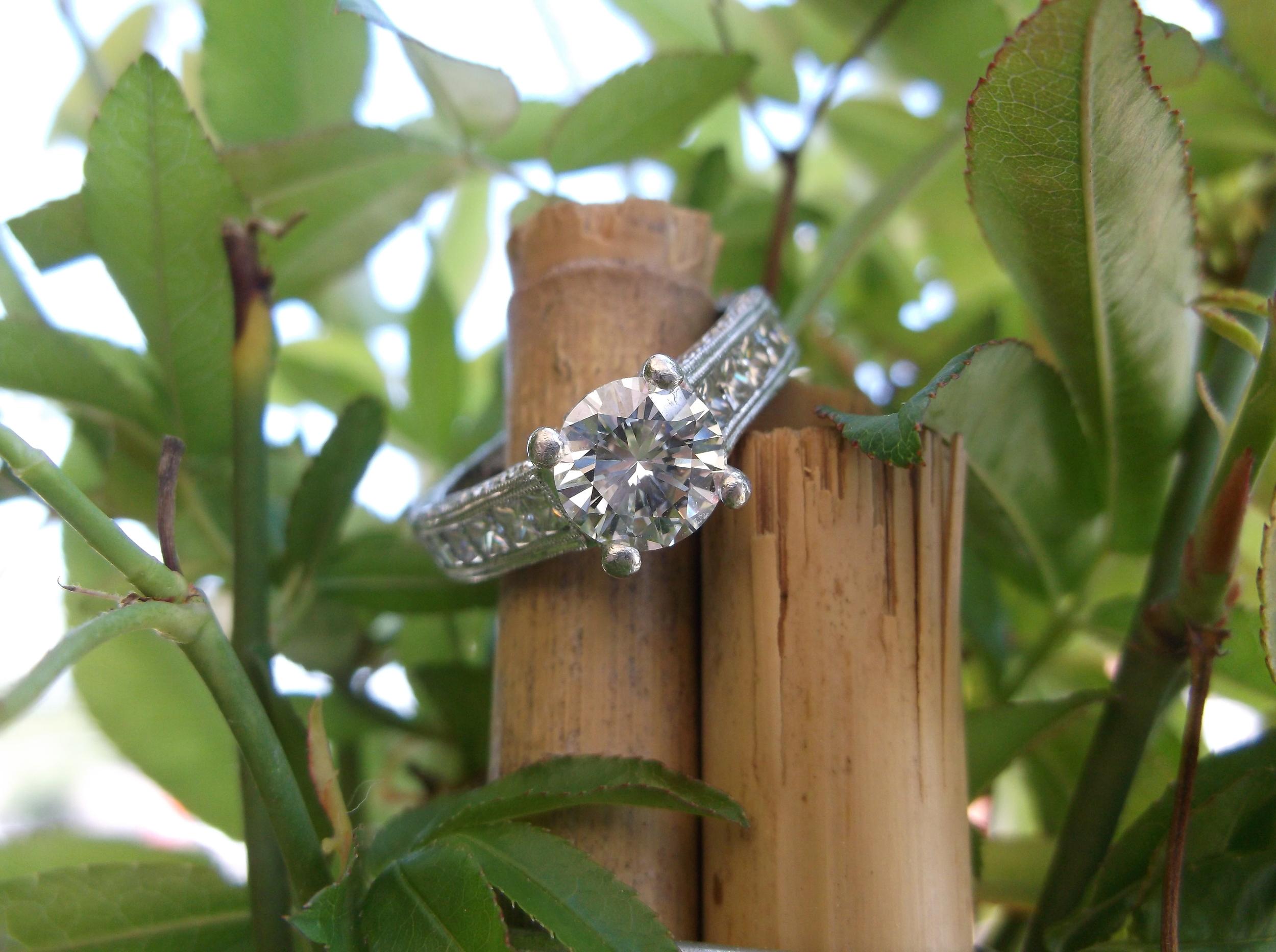 SOLD - Gorgeous 1.26 carat round brillant diamond set in platinum with beautiful diamond detail down each side.