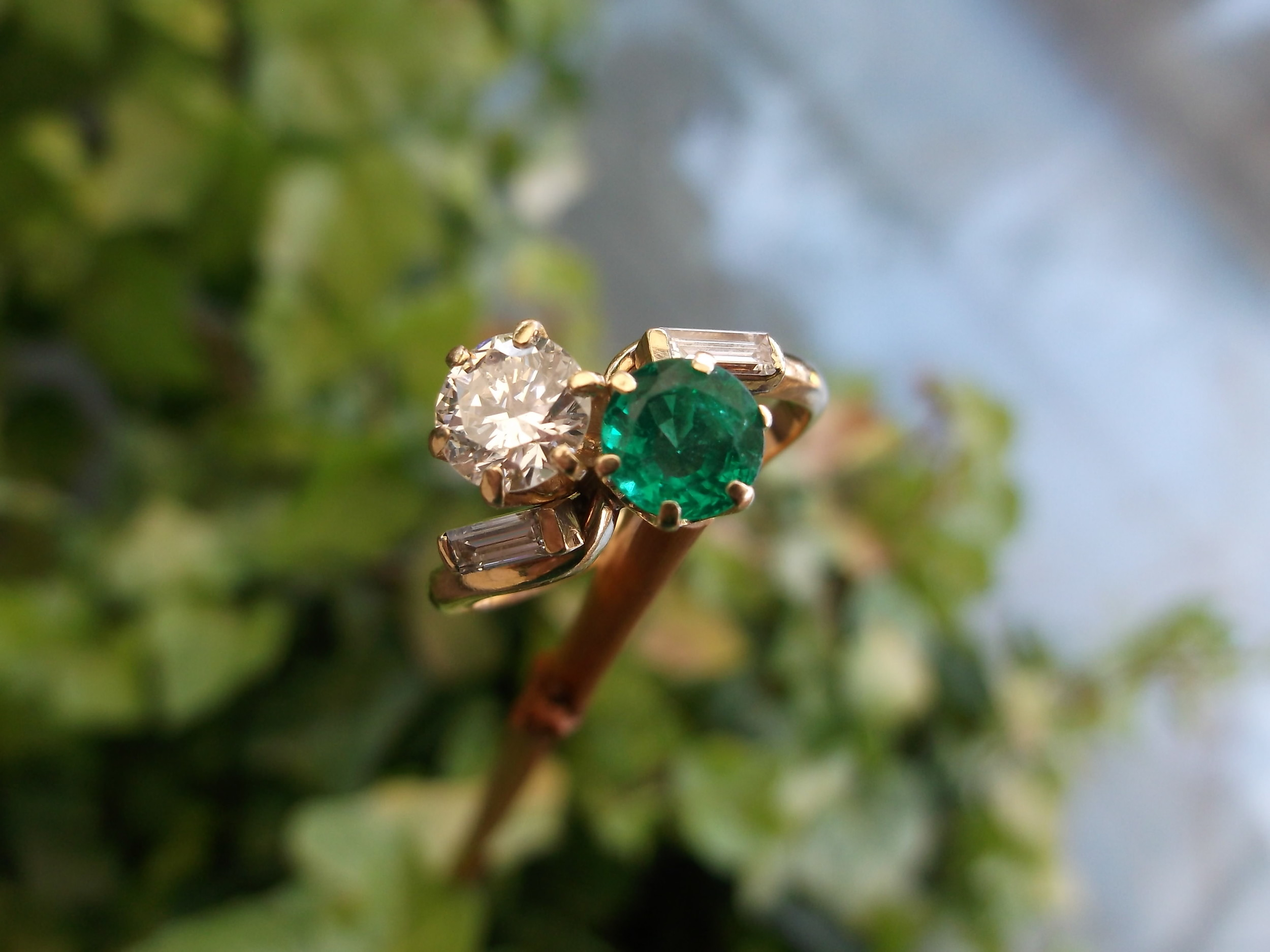 SOLD - Beautiful 1950's diamond and emerald bypass ring with a 0.80 carat round brillant diamond and a 0.70 carat emerald set in 14K yellow gold with baguette diamond detail.