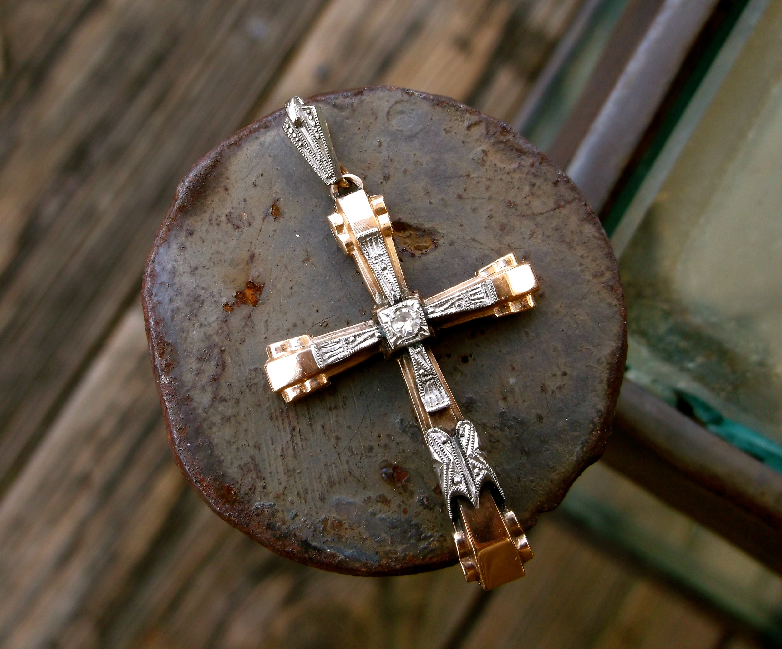 Edwardian white gold on yellow gold cross with a diamond in the center.