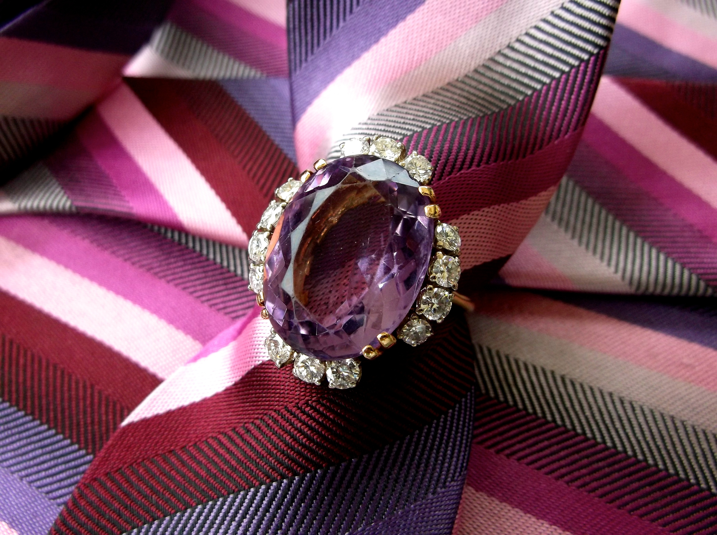SOLD - Impressive 15.0 carat amethyst ring surrounded by 1.40 carats total weight in diamonds set in yellow gold.