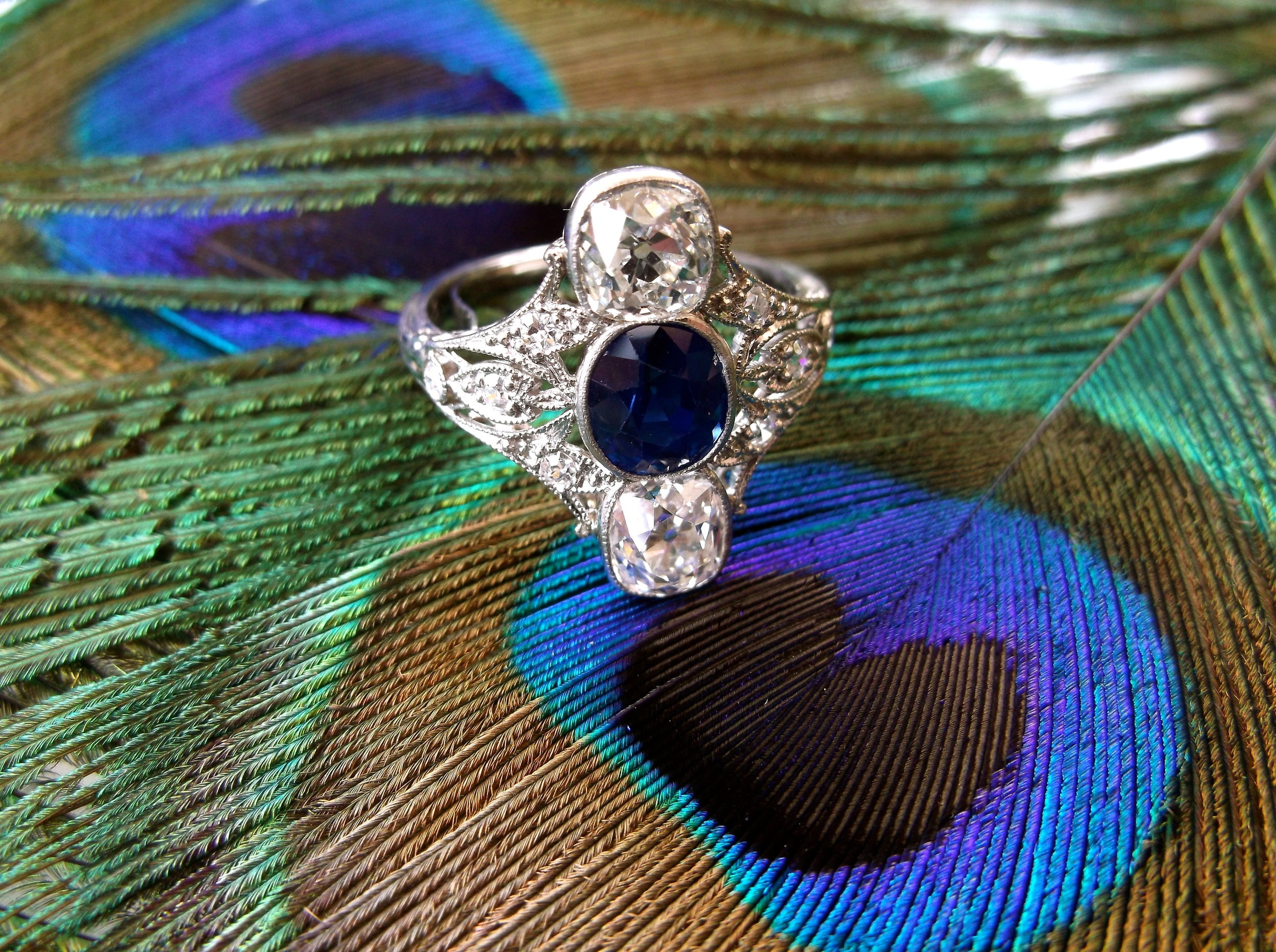 SOLD - Jaw dropping Art Deco Old Mine cut diamond and sapphire ring set in platinum. (0.88 carats between the two larger Old Mine cut diamonds and a 1.20 carat sapphire in the center)