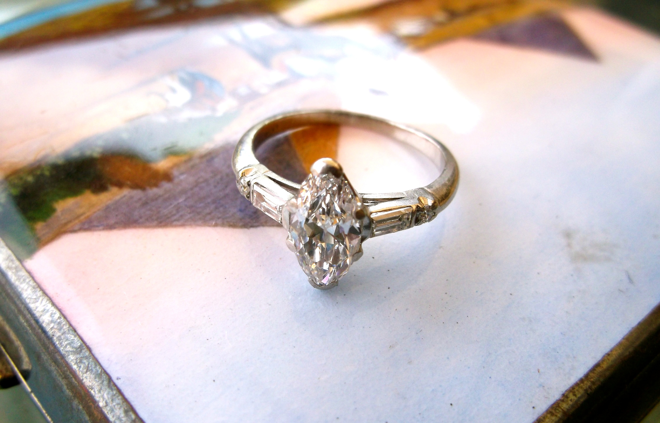 SOLD - All original 1930's 0.85 carat Old European cut marquis diamond set in platinum with baguette and round diamond detail on either side.