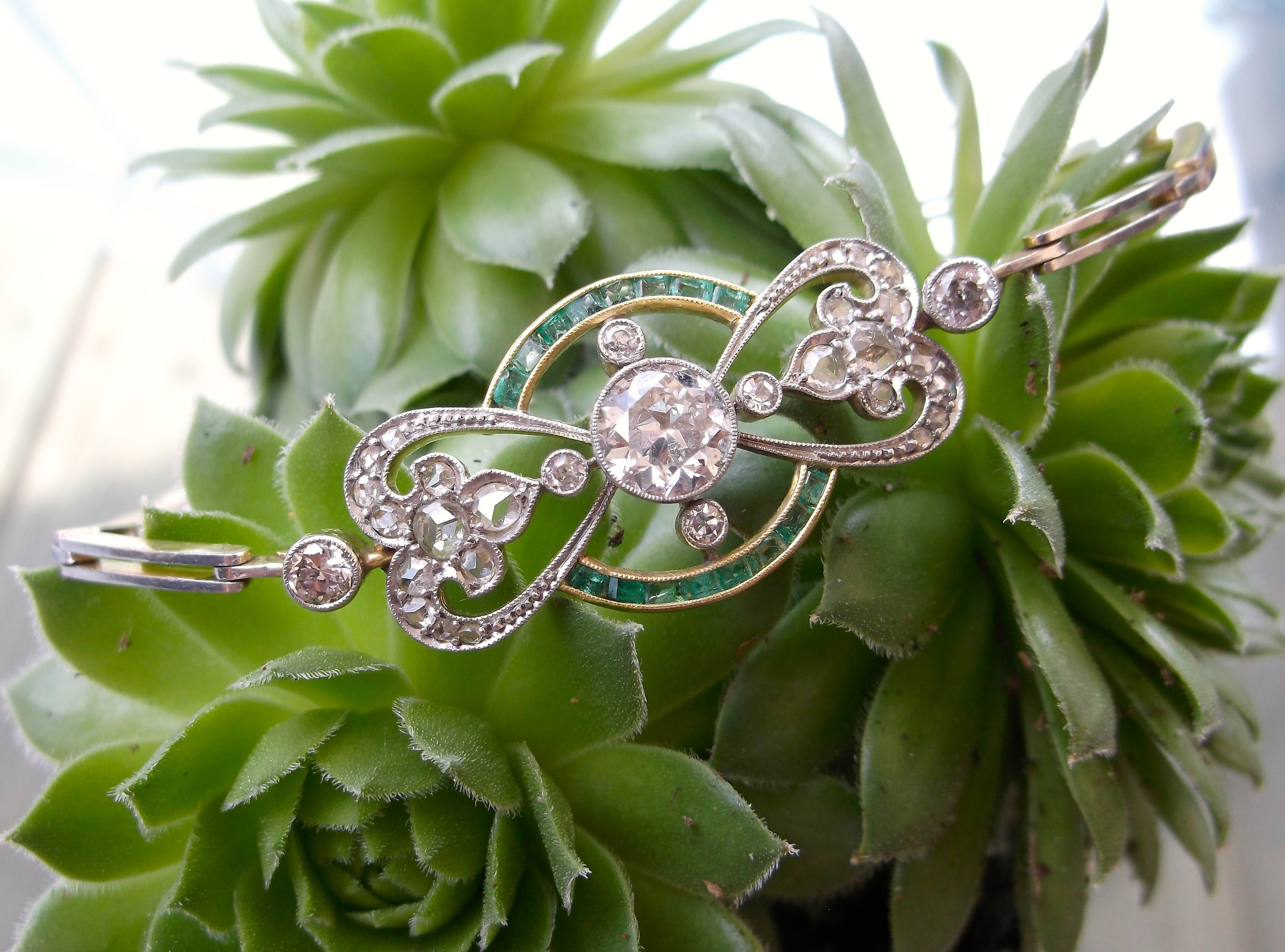 SOLD - tunning Edwardian Era Old European cut diamond and emerald detail bracelet set in platinum topped gold with a 1.15 carat Old European cut diamond in the center.