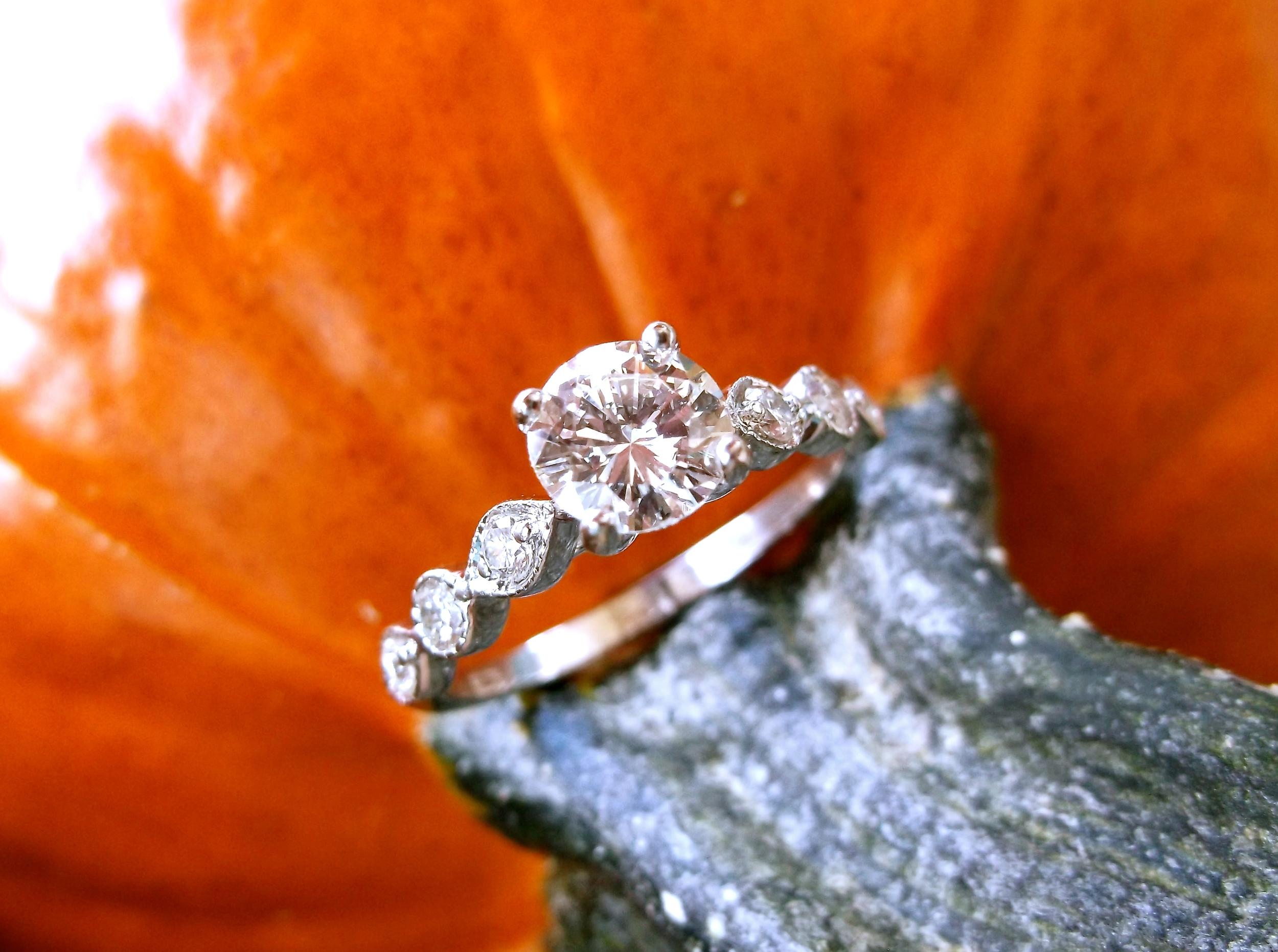 Beautiful 0.70 carat diamond set in a classic white gold and diamond setting.