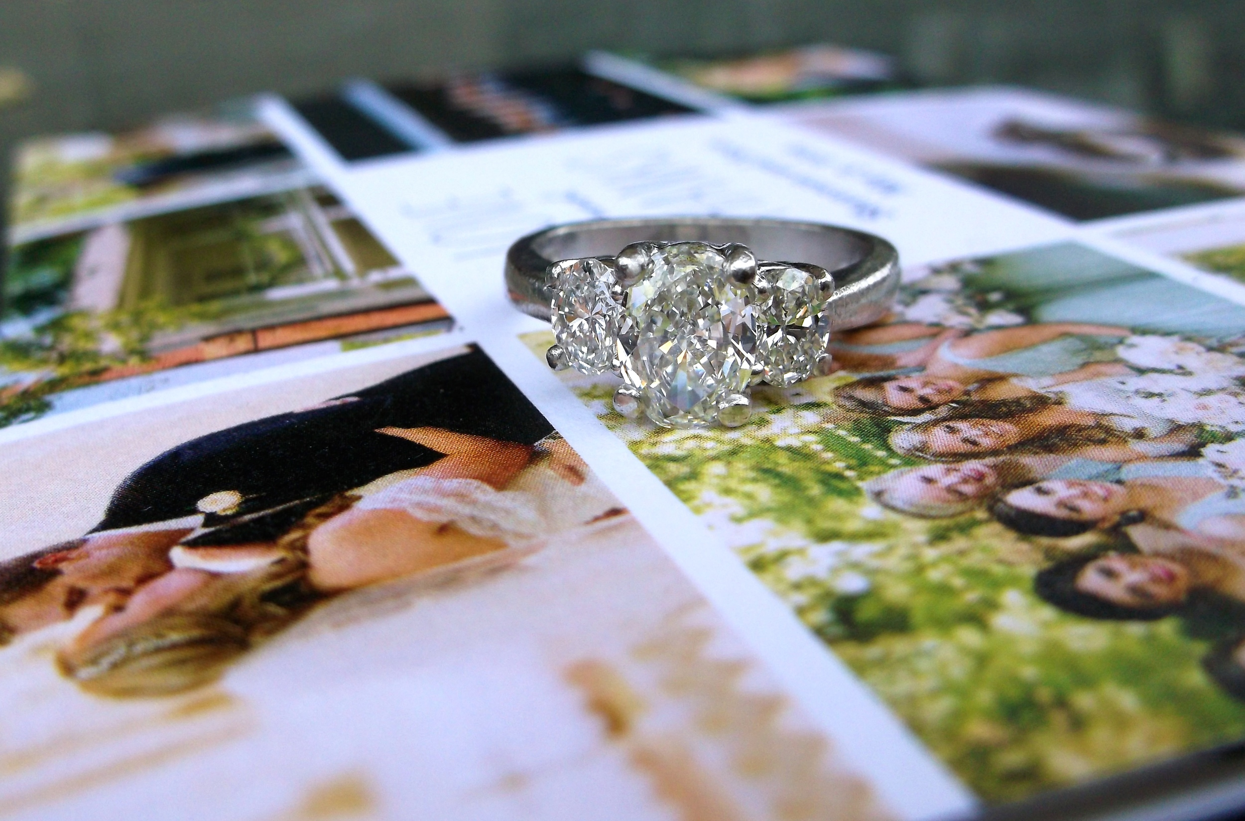 SOLD - Gorgeous three stone oval diamond ring set in platinum with a 0.95 carat diamond in the center and a 0.33 carat diamond on either side.   Thank you to Shannon and Scott for sending us such a lovely not with beautiful pictures from your wedding! We are honored to be a part of your story!