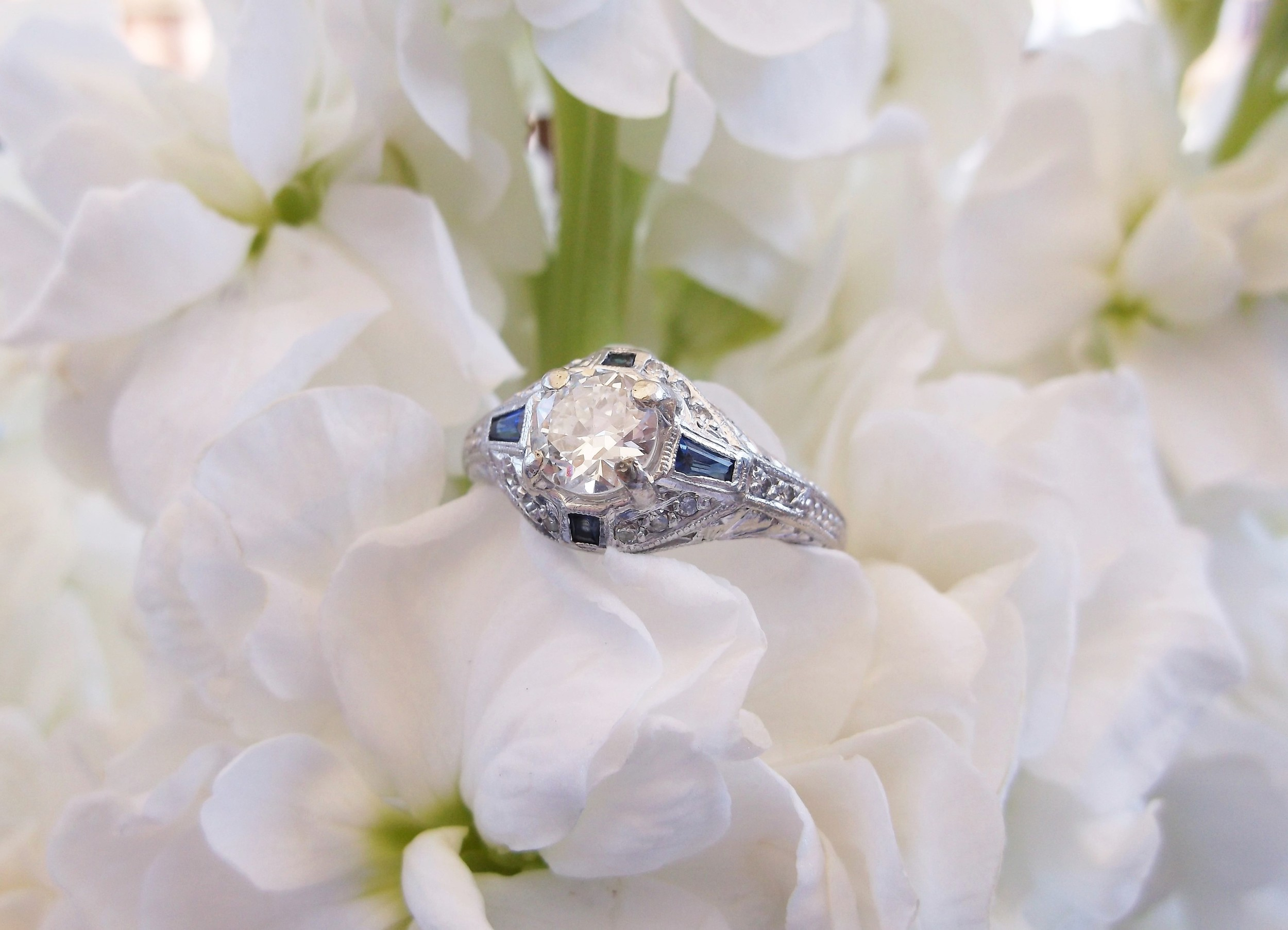 SOLD - 1920's Old European cut diamond ring with beautiful sapphire detail set in platinum with a 0.58 carat diamond in the center.