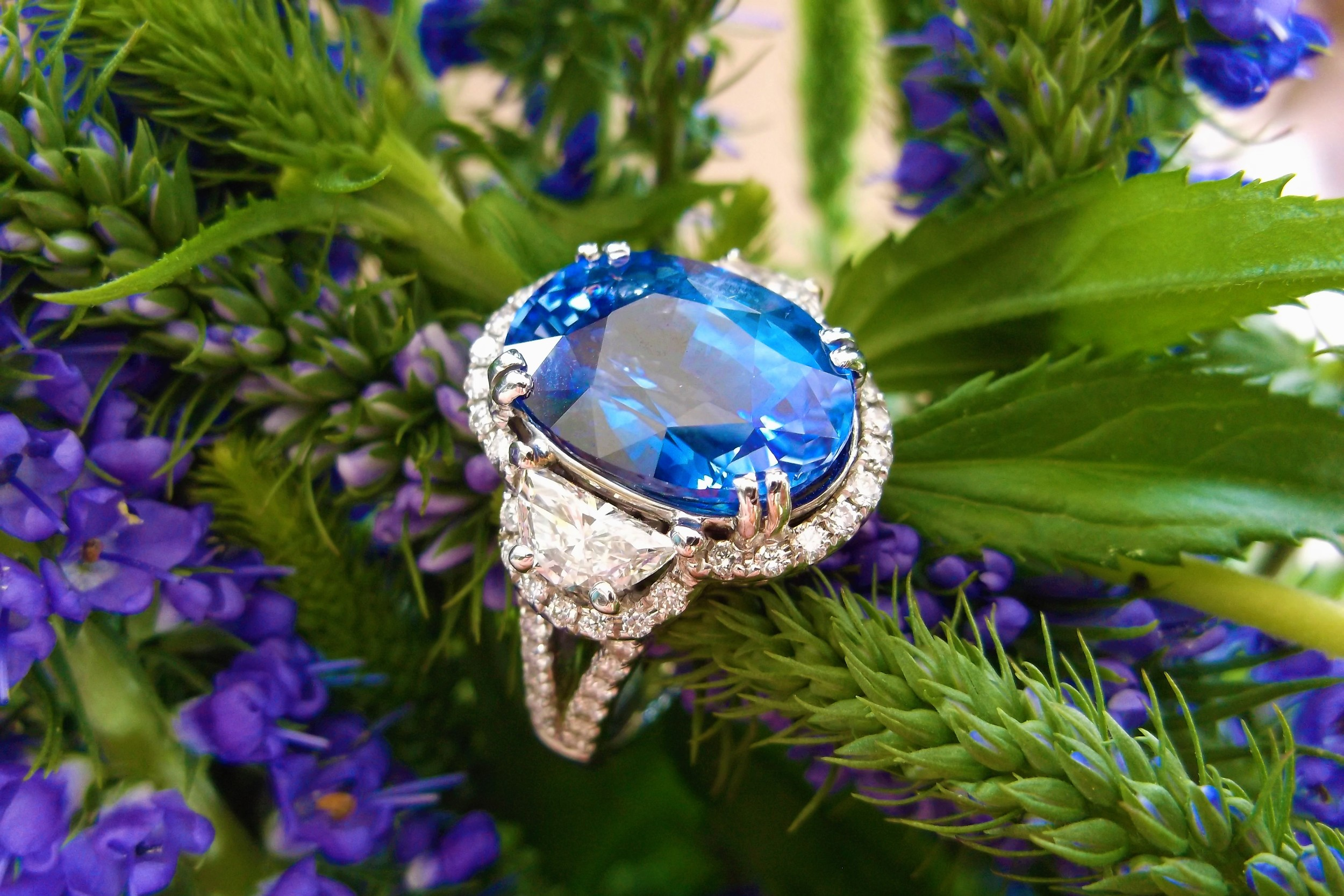 Stunningly gorgeous 8.52 carat sapphire with a half moon shaped diamond on each side surrounded by round diamonds set in white gold (1.24 carats total weight in diamonds!).