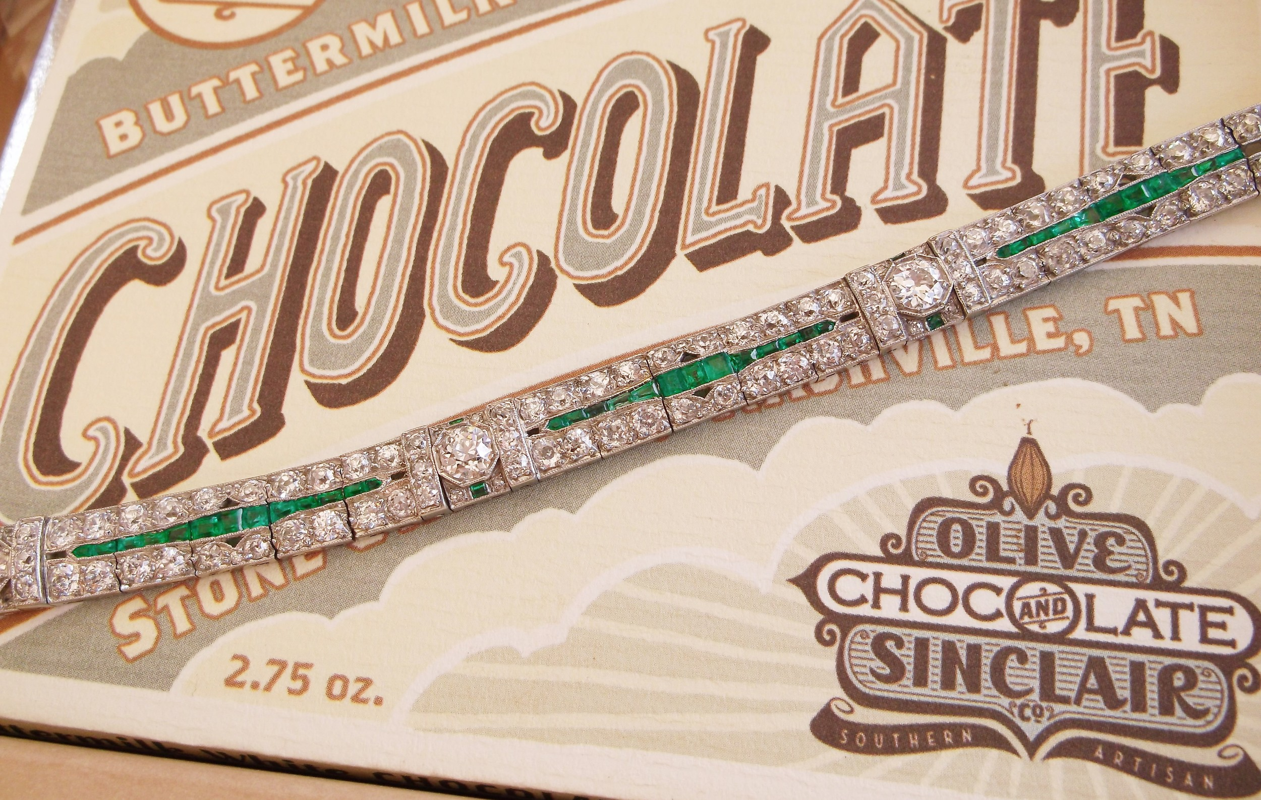 Gorgeous 1920's diamond, emerald and platinum bracelet that features over 11.00 carats total weight of Old European cut diamonds! Pictured on a delicious chocolate bar from  Olive and Sinclair Chocolate Co.  (Whom we've heard may soon be opening on Main Street in Downtown Franklin!)