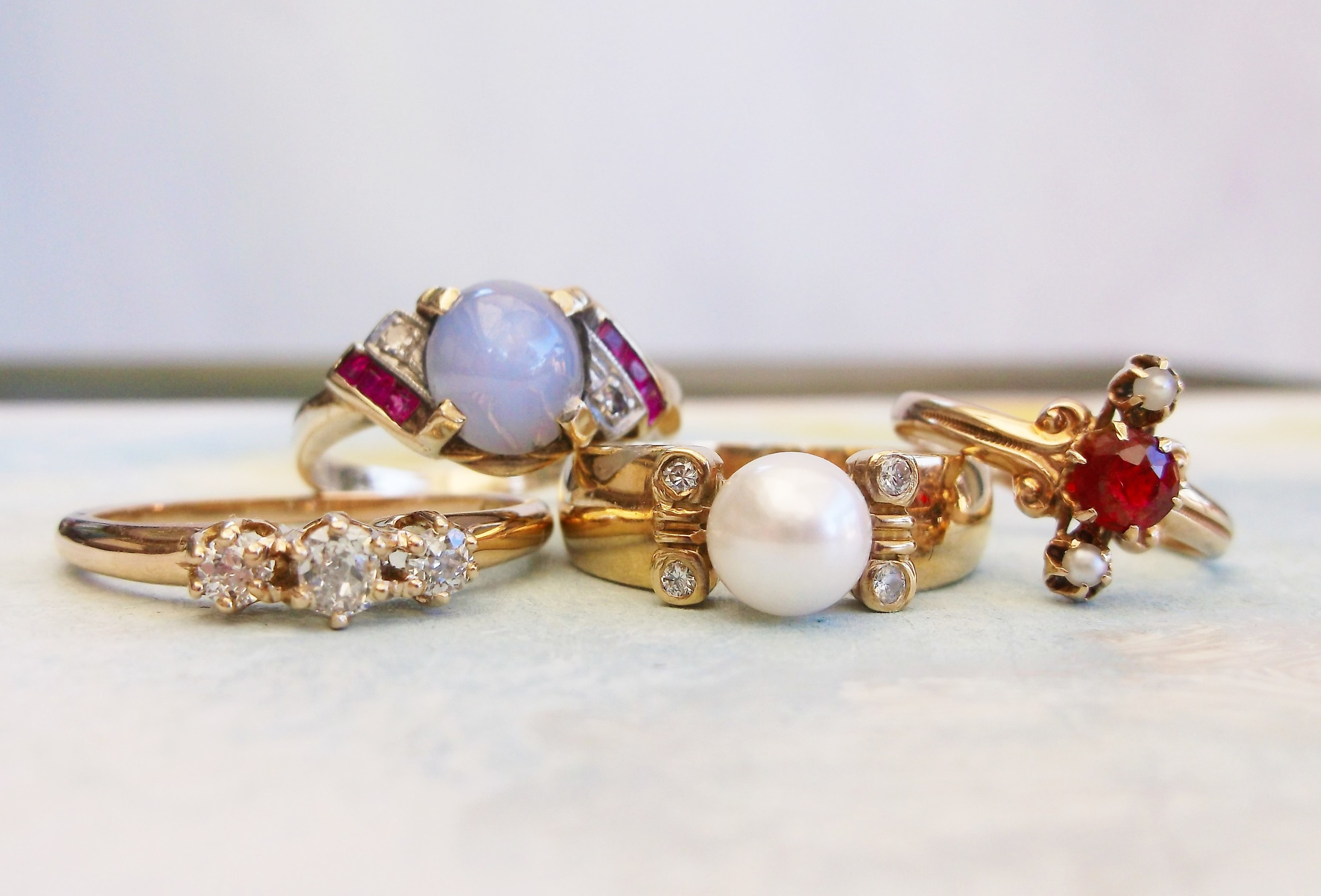 From Left to Right:  *SOLD - Three stone Old Mine cut diamond ring with 0.25 carats total weight in diamonds set in 14K yellow gold. *SOLD - Retro star sapphire, ruby and diamond ring set in 10K yellow gold. *SOLD - 18K yellow gold, pearl and diamond ring. ... *SOLD - Victorian pearl and garnet doublet ring set in 14K yellow gold.