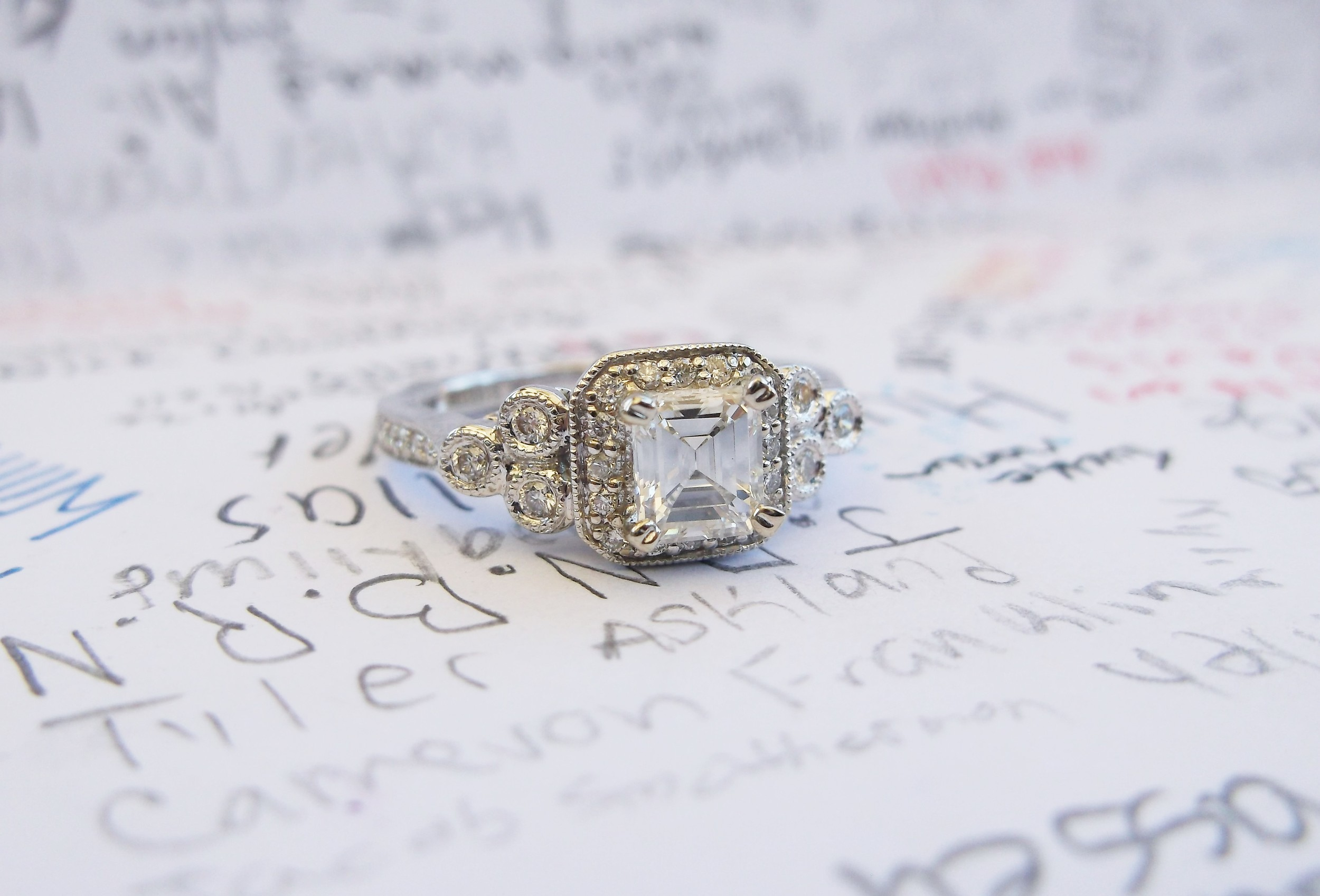 SOLD - Beautiful 0.49 carat emerald cut diamond set in a lovely white gold and diamond detail mounting.